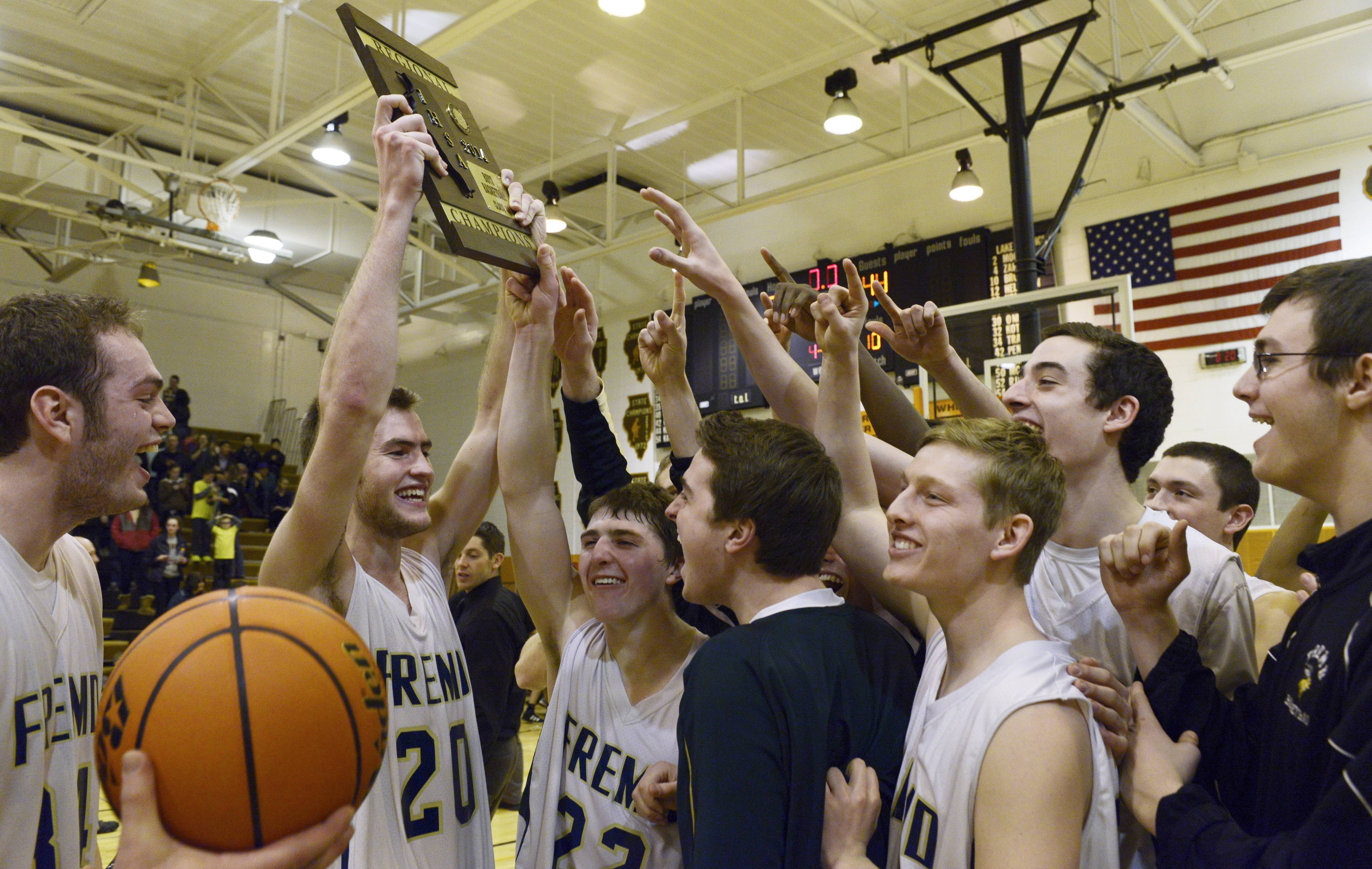 Fremd's Riley Glassmann holds up the championship plaque as the team celebrates its 58-44 victory over Lake Zurich.