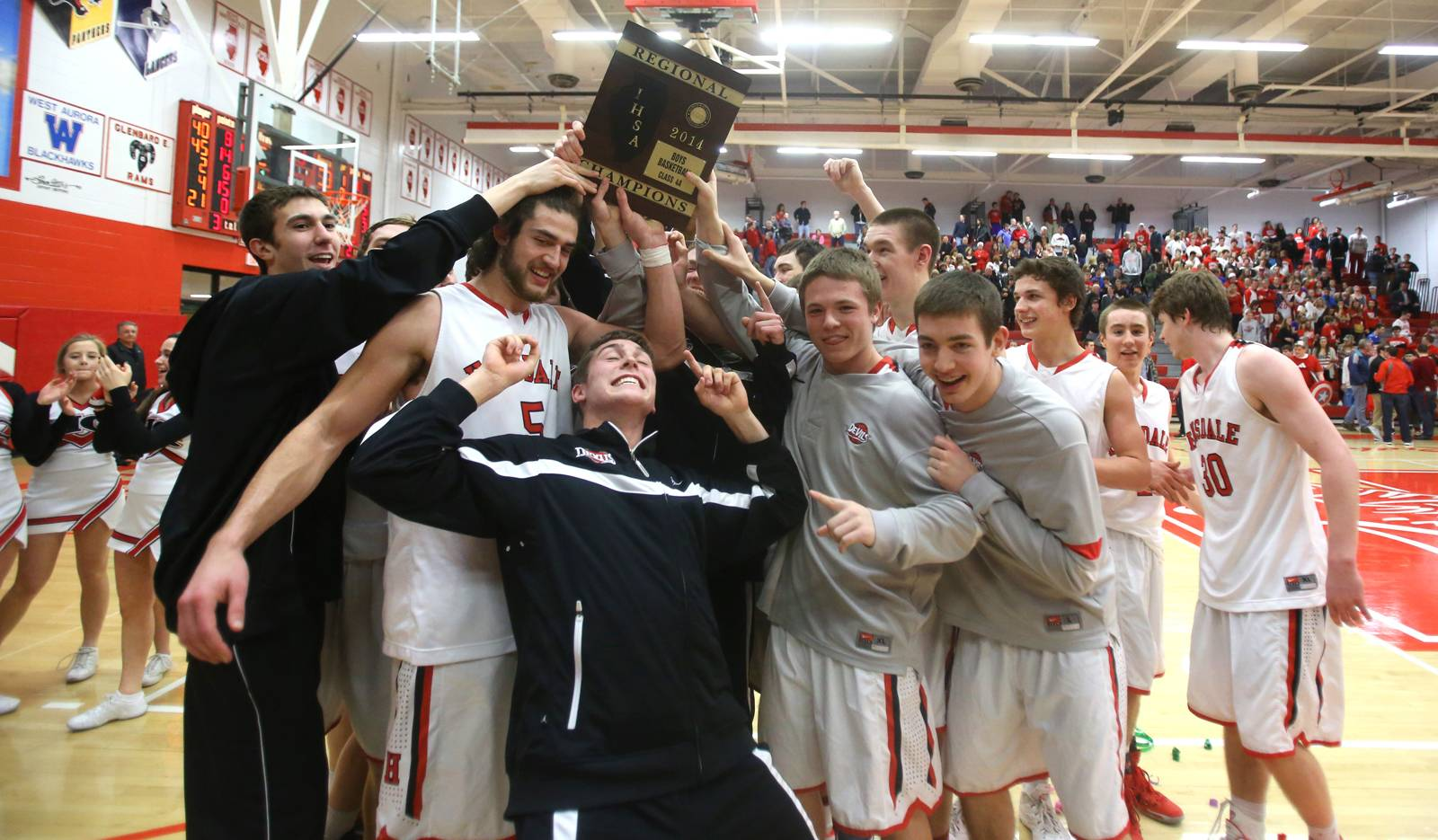 Hinsdale Central players celebrate their regional boys basketball championship win over Naperville Central.