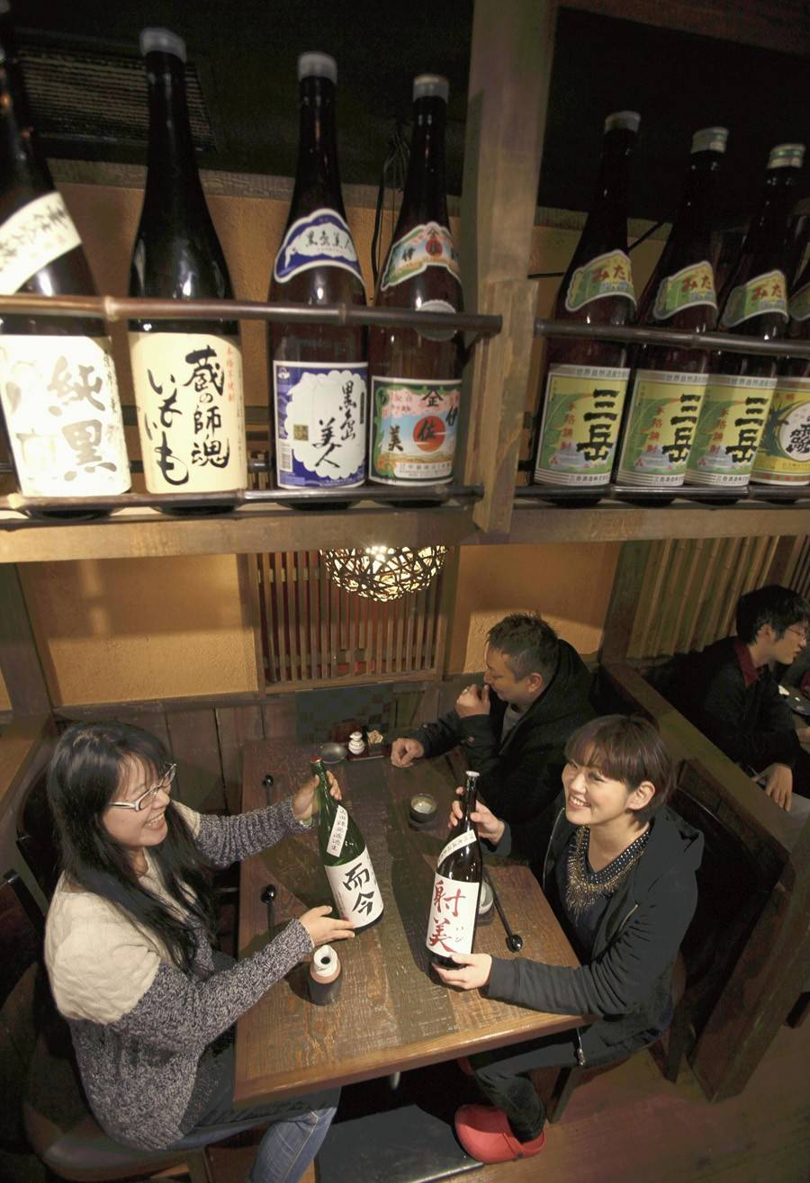 Patrons check bottles of sake at an izakaya in Tokyo, where Japanese specialties are served.