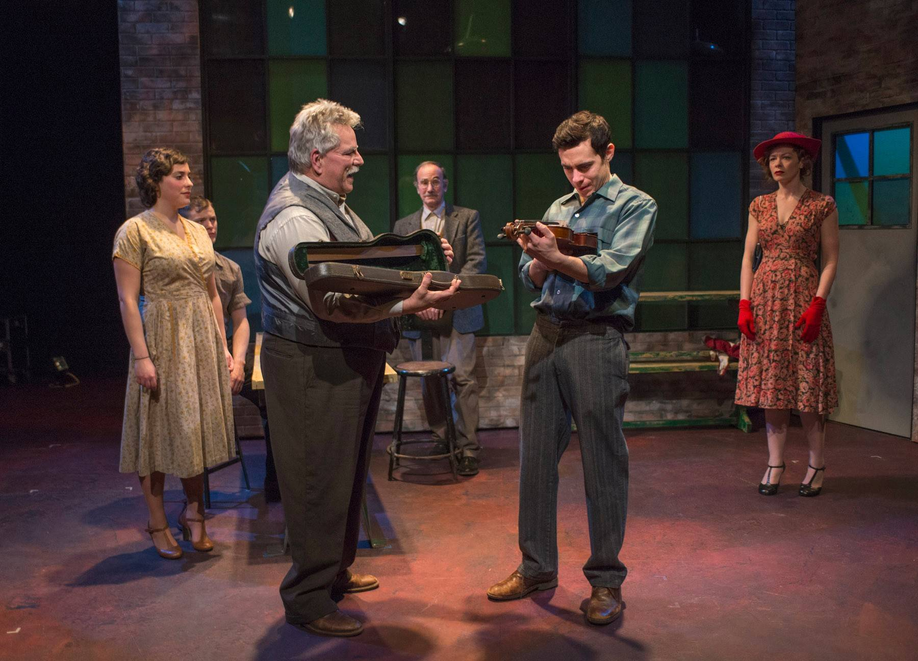 "As he prepares to embark on a prizefighting tour, the conflicted Joe (Nate Santana), second from right, receives a violin from his father (Norm Woodel), third from left, in Griffin Theatre's ""Golden Boy."" Jonathan Berry's fine production also features Laura Lapidus, left, Morgan Maher, Jerry Bloom and Nina O'Keefe."