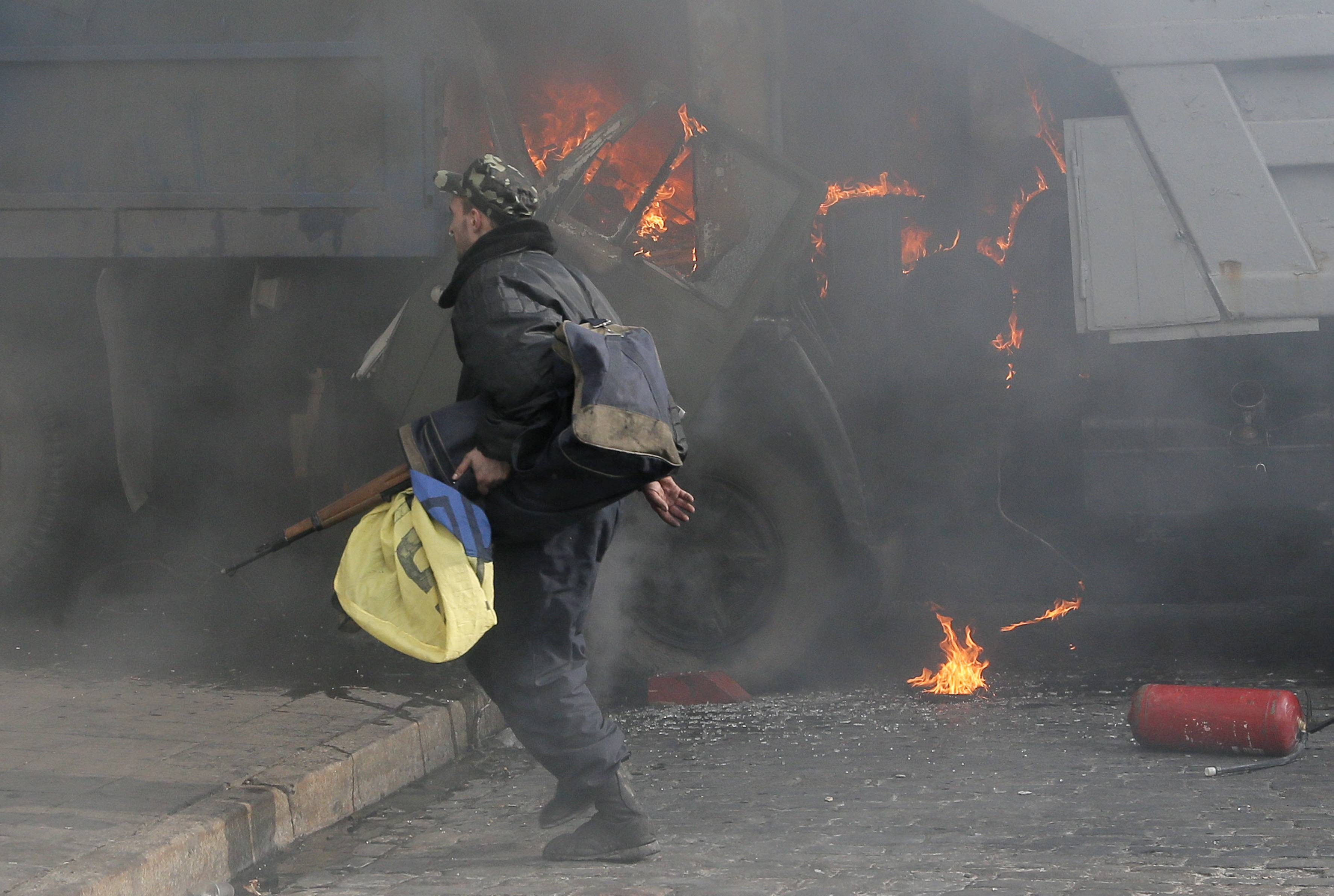 A man with a gun runs along a street during a clash between opposition protesters and riot police near the Presidential office in Kiev, Ukraine. As questions circulate about who was behind the lethal snipers that sowed death and terror in Ukraine's capital, doctors and others told the AP the similarity of bullets wounds suffered by opposition victims and police indicates the snipers were specifically trying to stoke tensions and spark a larger, angrier clash between opposition fighters and government security forces.