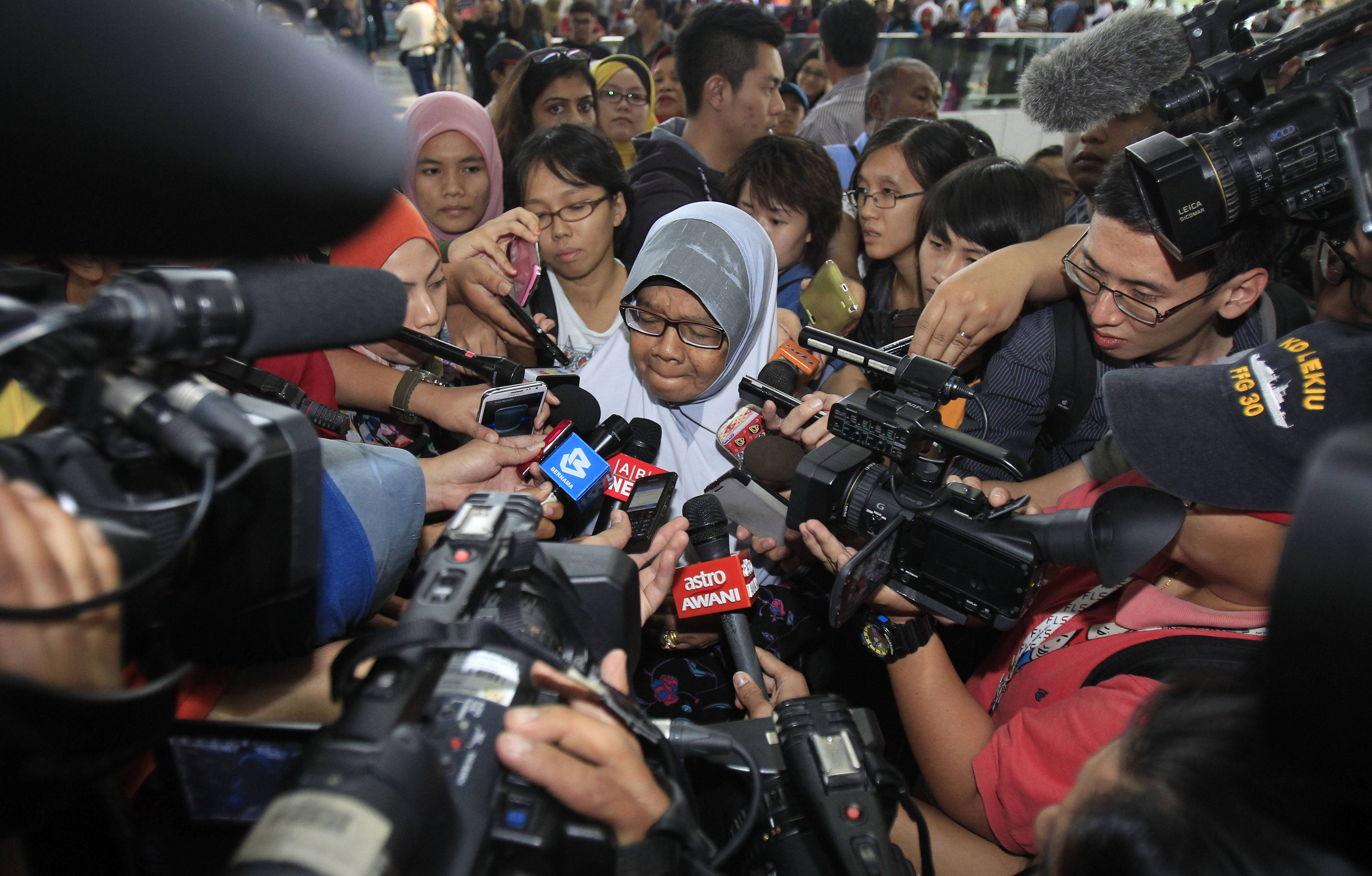 A family member of passengers aboard a missing Malaysia Airlines plane is mobbed by journalists at Kuala Lumpur International Airport in Sepang, outside Kuala Lumpur, Malaysia, Saturday.