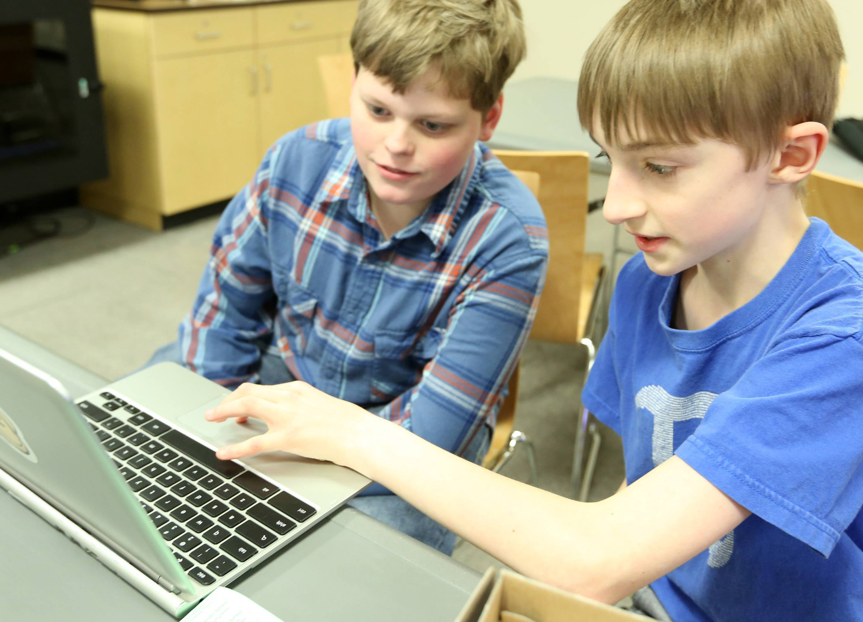 "Andrew Cluff, 13, left, and Andy Merrill, 12, both of Libertyville, discuss computers Friday during a teen program called ""Teen Tinkers and Minecraft"" at Cook Memorial Library in Libertyville."