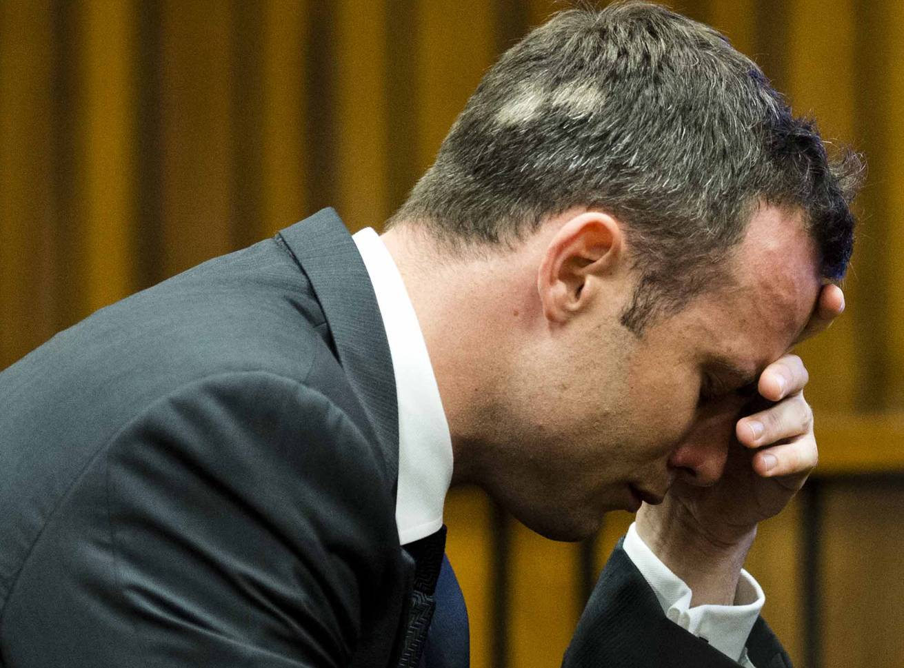 Oscar Pistorius, puts his hand to his face while listening to cross questioning about the events surrounding the shooting death of his girlfriend Reeva Steenkamp, during his trial in Pretoria, South Africa, Friday.