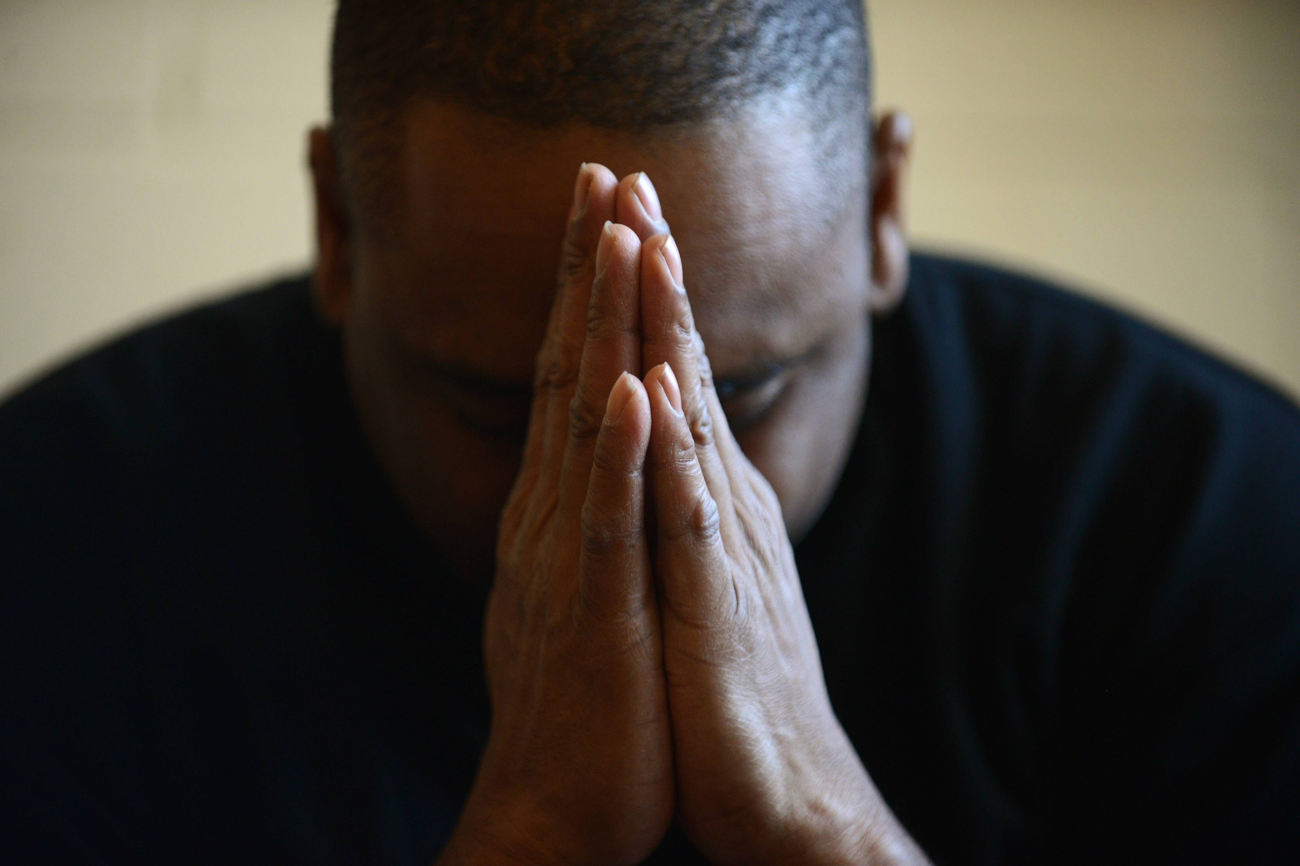 Edward Hayes of Elgin bows his head during a prayer group at Vineyard Church of Elgin. Hayes was homeless and addicted to cocaine before members of the church and their breakfast ministry helped to get him into a rehab program. He's been clean for three years and has volunteered at the church every day since.