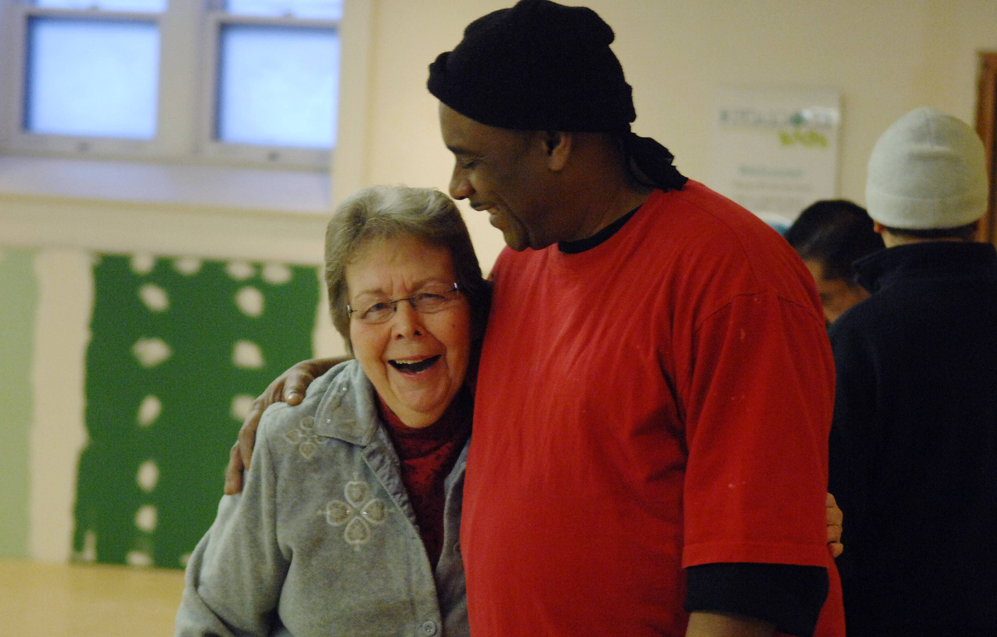 Nancy Merlak gets a hug from Edward Hayes of Elgin during the morning breakfast ministry at Vineyard Church of Elgin. She was among a group of members who helped and encouraged Hayes to get into a rehab program and get off the streets.