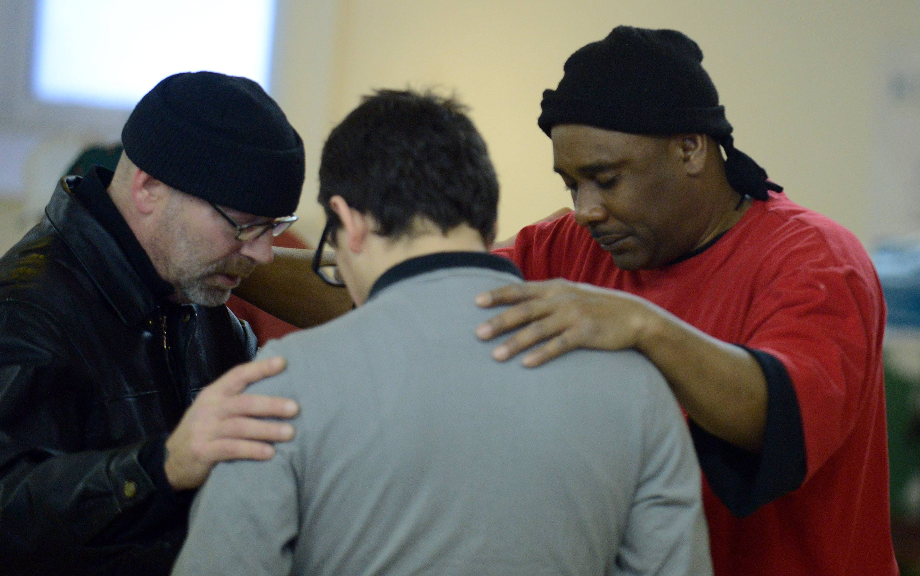 Greg Schiller of Street Reach, left, and Edward Hayes, right, pray with a young man with a drug problem who they persuaded to go to rehab during the breakfast ministry at Vineyard Church of Elgin.