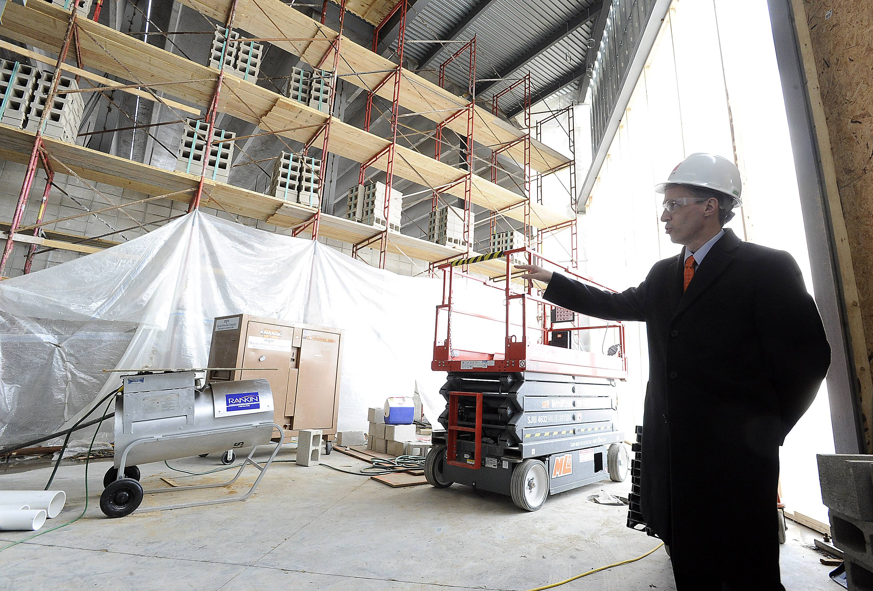 Ted Birren, director of operations at District 214, points out where the new lockers and dressing rooms will go.