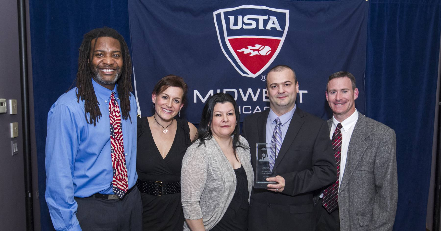 Chicago USTAPhoto Release: From left to right: Oak Brook Park District Tennis Center Representatives Andre Dockens, Tennis Professional; Brooke Wedding, Tennis Professional;  Leticia Limonez, Assistant Tennis Center Manager; Alin Pop, Tennis Center Manager; and Roger Emig, Tennis Professional accept the 2013 award for Outstanding Facility of the Year from the Chicago USTA during the 25th Annual Evening of Champions.