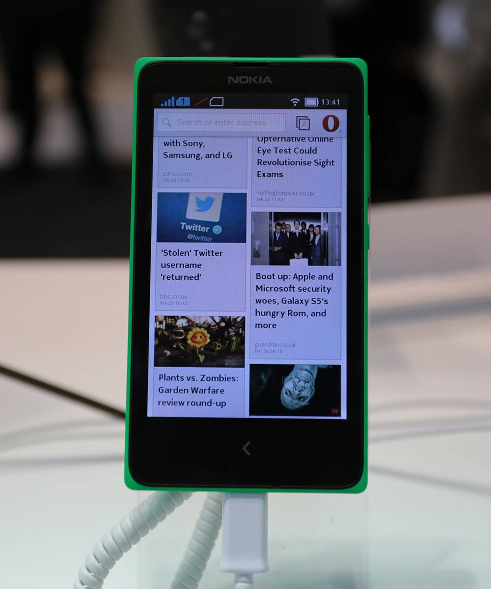 An employee displays a Nokia X smartphone for a photograph at the Nokia Oyj pavilion on the opening day of the Mobile World Congress in Barcelona, Spain, on Monday, Feb. 24, 2014.
