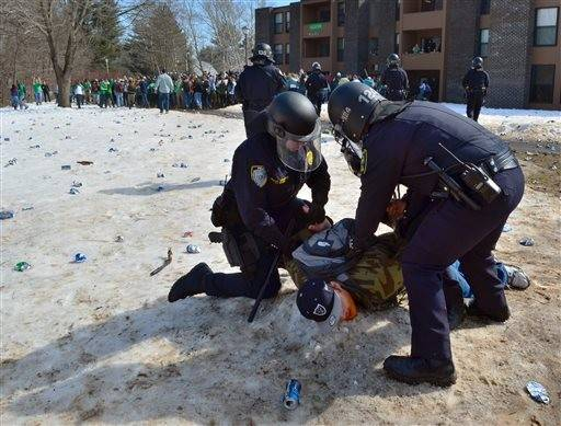 "Police detain a participant Saturday in the pre-St. Patrick's Day ""Blarney Blowout"" near the University of Massachusetts in Amherst, Mass."