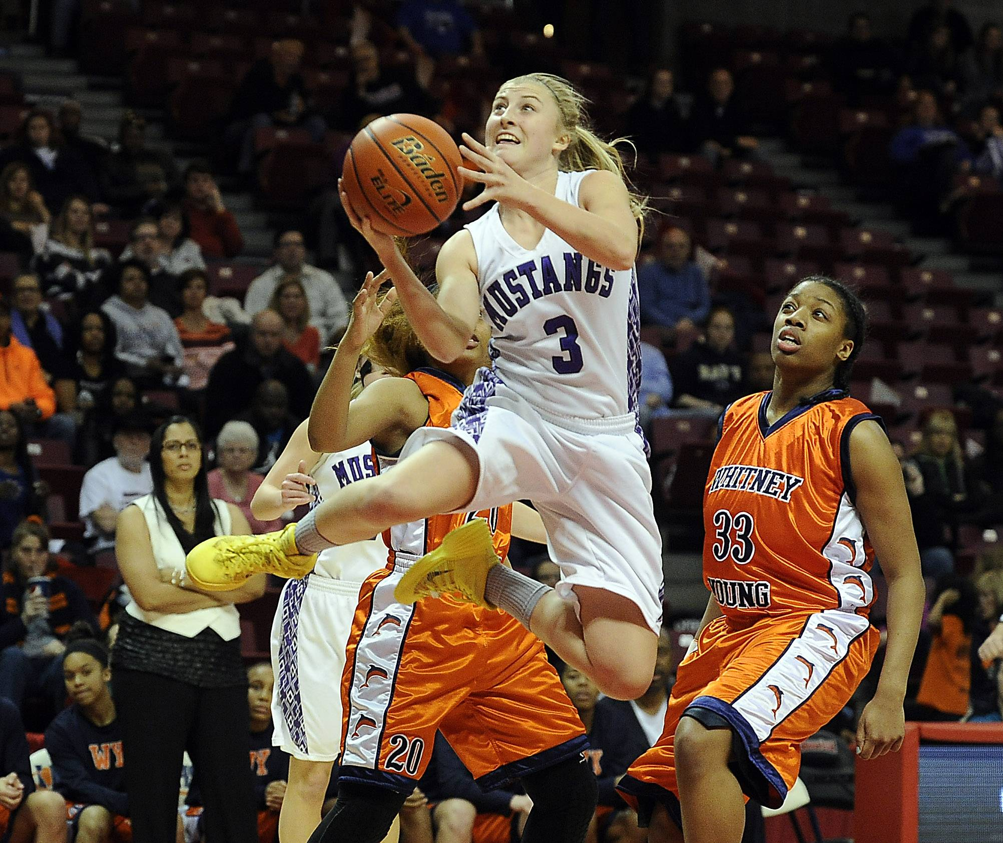 Rolling Meadows senior Jackie Kemph flies through the air past Whitney Young defenders in the first half of the Class 4A state championship game in Normal on Saturday.