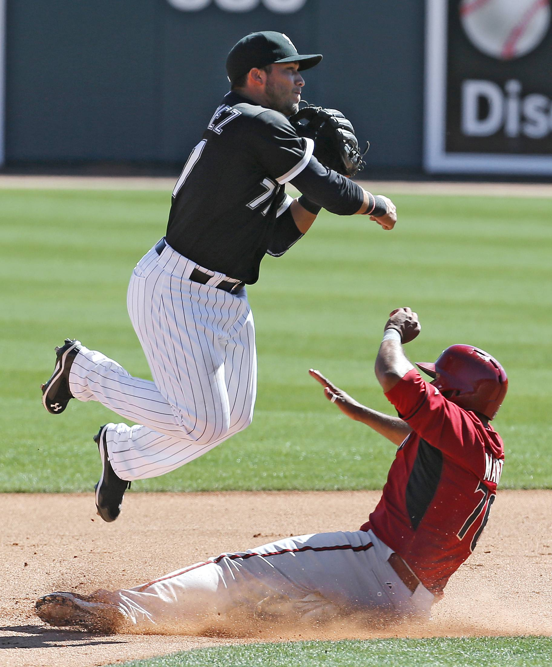 Chicago White Sox second baseman Carlos Sanchez jumps over Arizona Diamondbacks' Andy Marte to complete a double play in the fourth inning during an exhibition baseball game in Glendale, Ariz., Saturday, March 8, 2014.