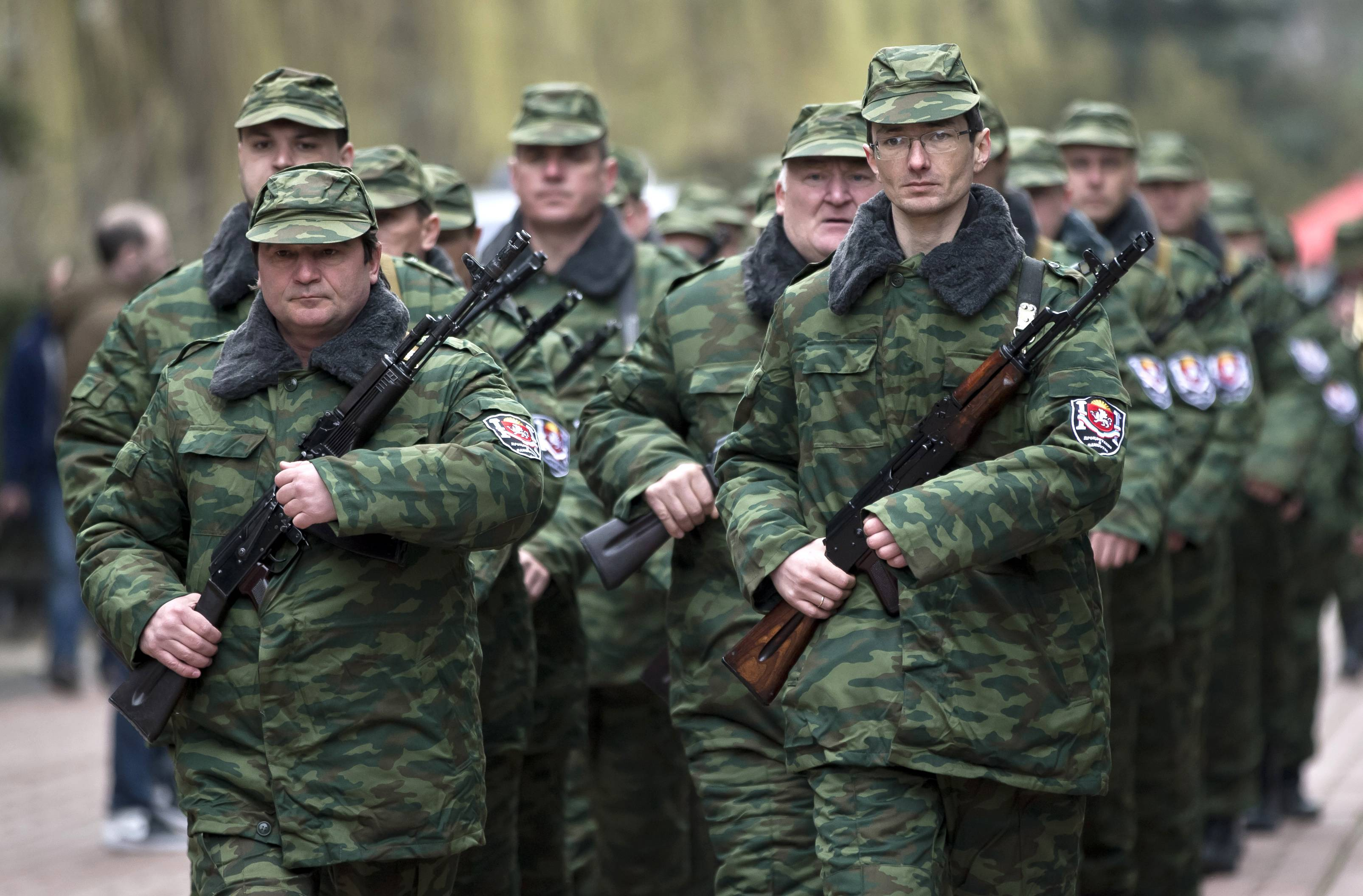 "Armed members of the first unit of a pro-Russian armed force, dubbed the ""military forces of the autonomous republic of Crimea"" march Saturday before the swearing-in ceremony in Simferopol, Ukraine"