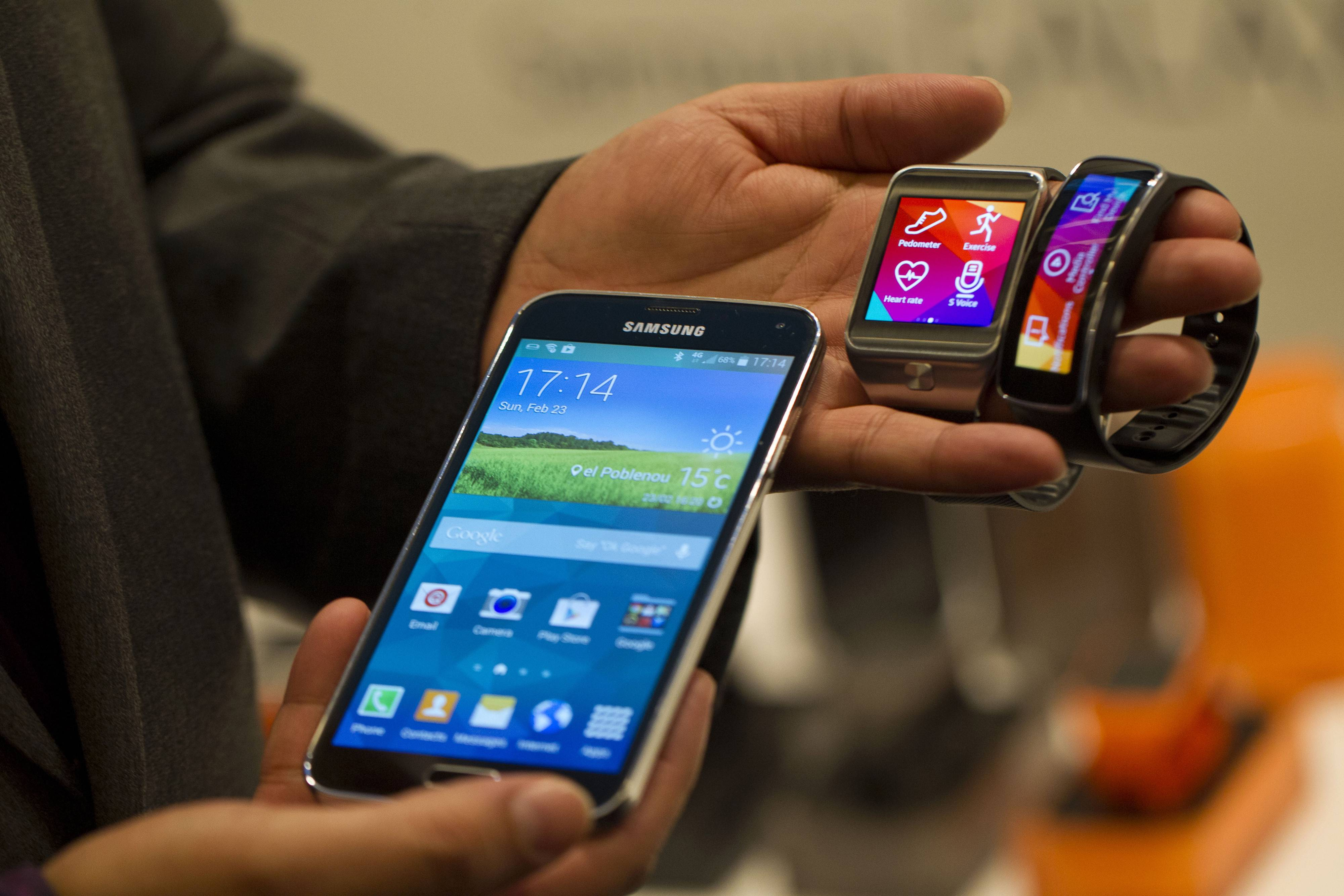 An employee displays a Galaxy S5 smartphone, left, and new Samsung Gear, center, and Gear Fit wristwatch devices during a Samsung Electronics Co. news conference ahead of the Mobile World Congress in Barcelona, Spain.