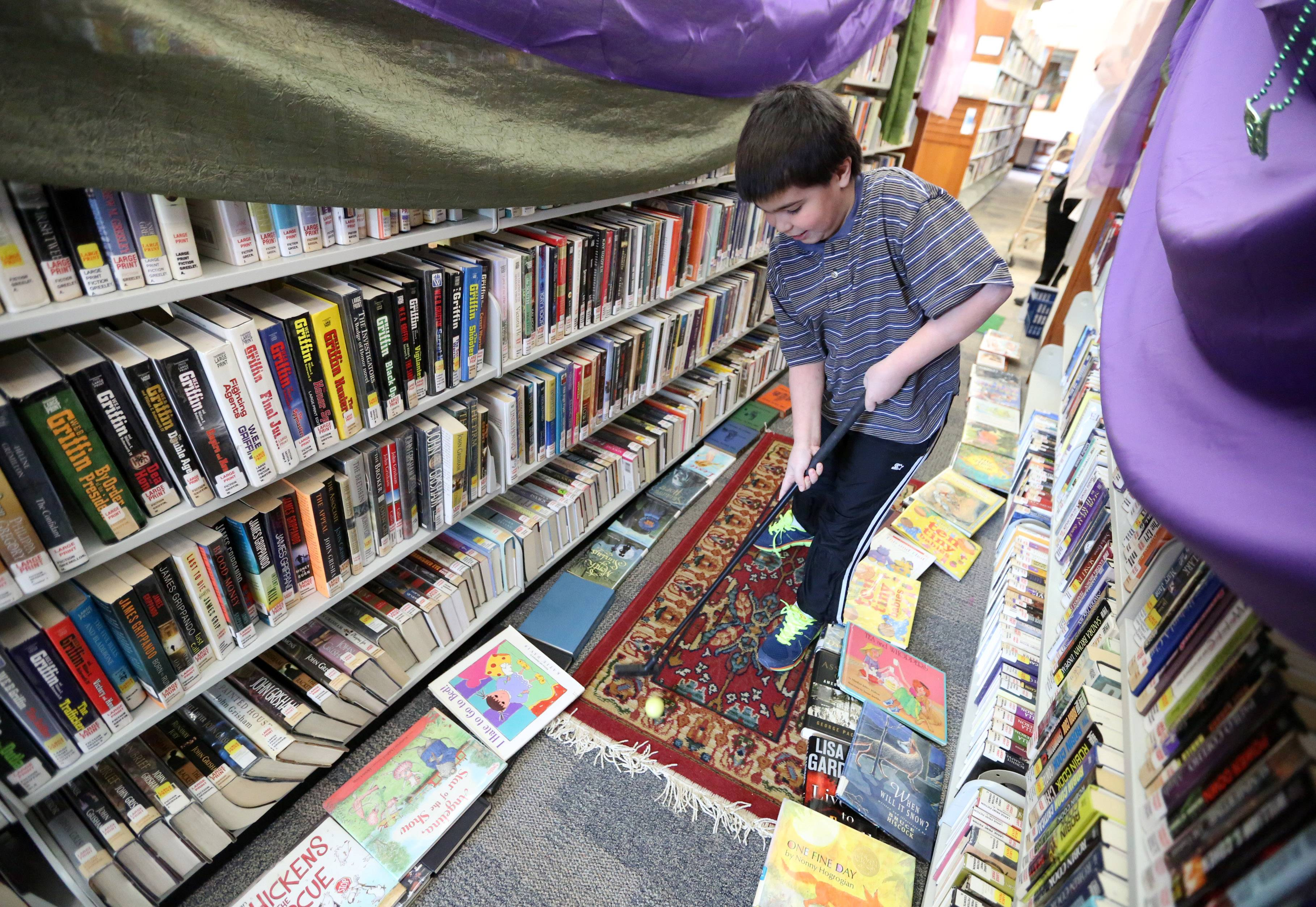 Zachary Krakow, 10, of Grayslake putts through a book aisle decorated with drapery to resemble an entry to a castle during mini-golf inside the Grayslake Area Public Library on Saturday in Grayslake.