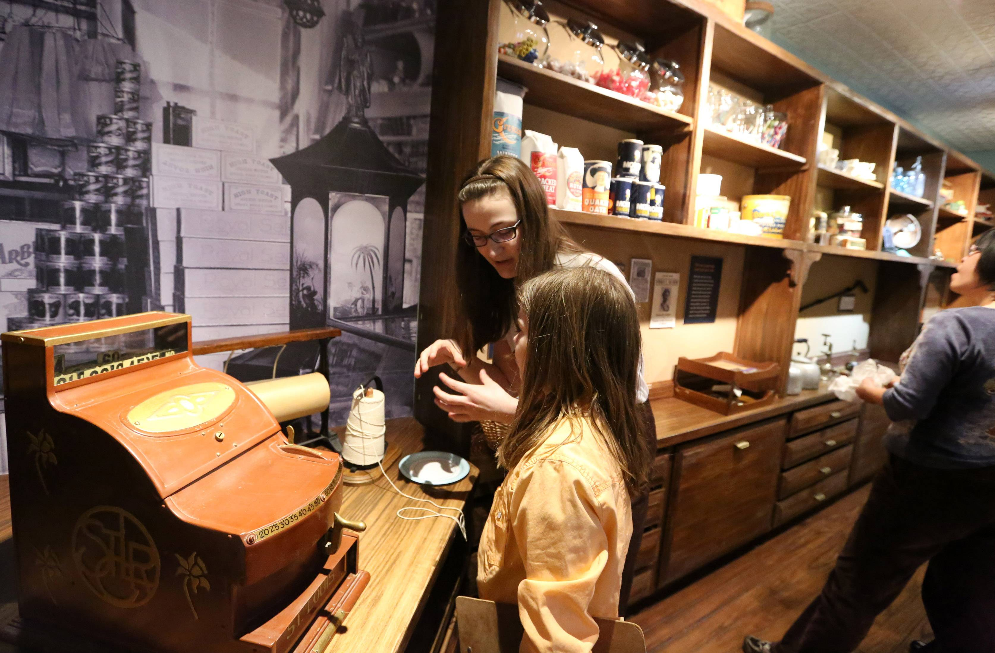 Heloise Jacobs, 9, and family friend Lindsey Wetle, 15, both of Buffalo Grove look for items on a scavenger hunt list Saturday in the Raupp Museum's newly renovated Crossroads exhibit's Weidner general store.