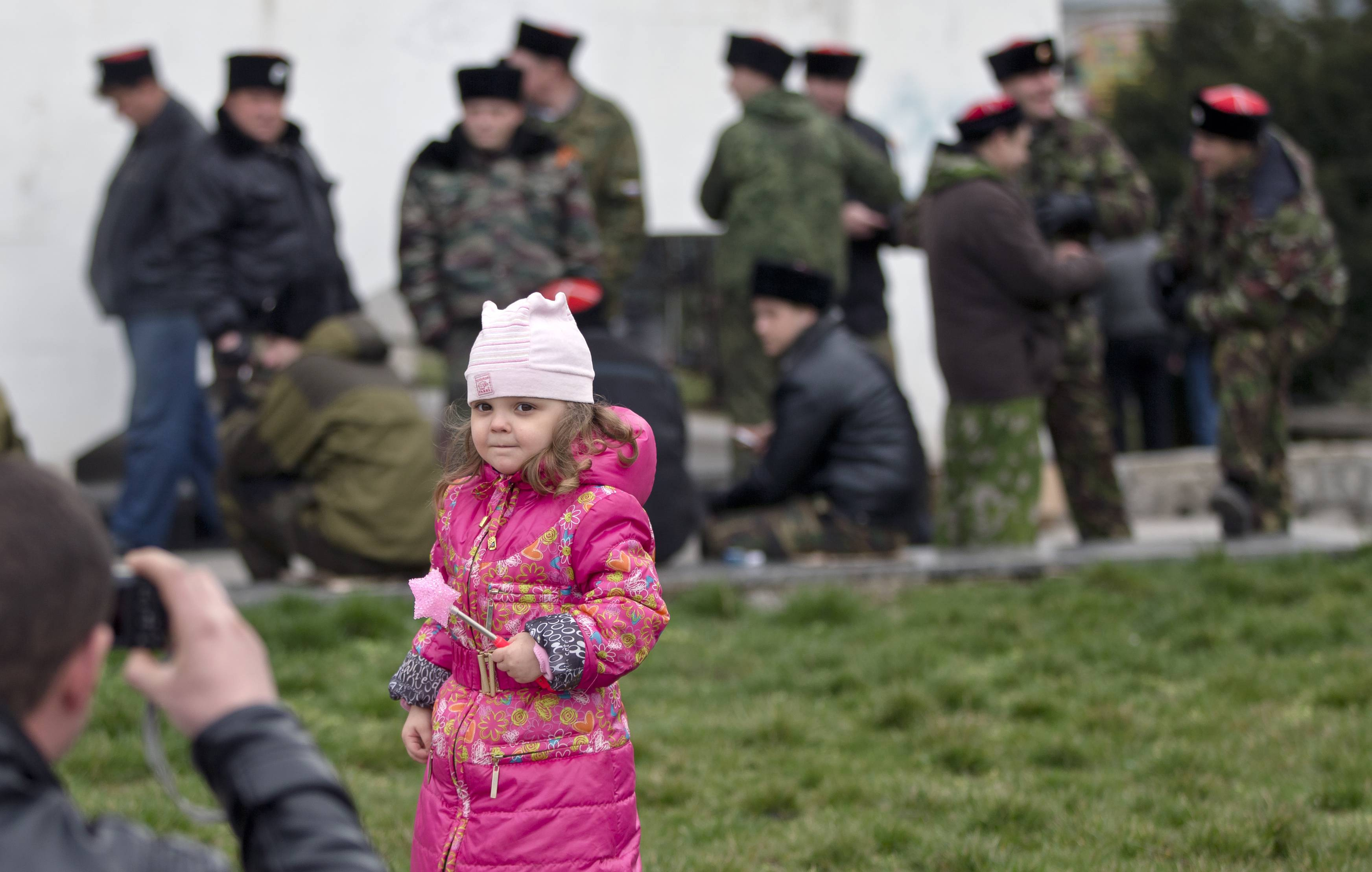 A man photographs a child Saturday with a group of Cossacks in the background in Simferopol, Ukraine.