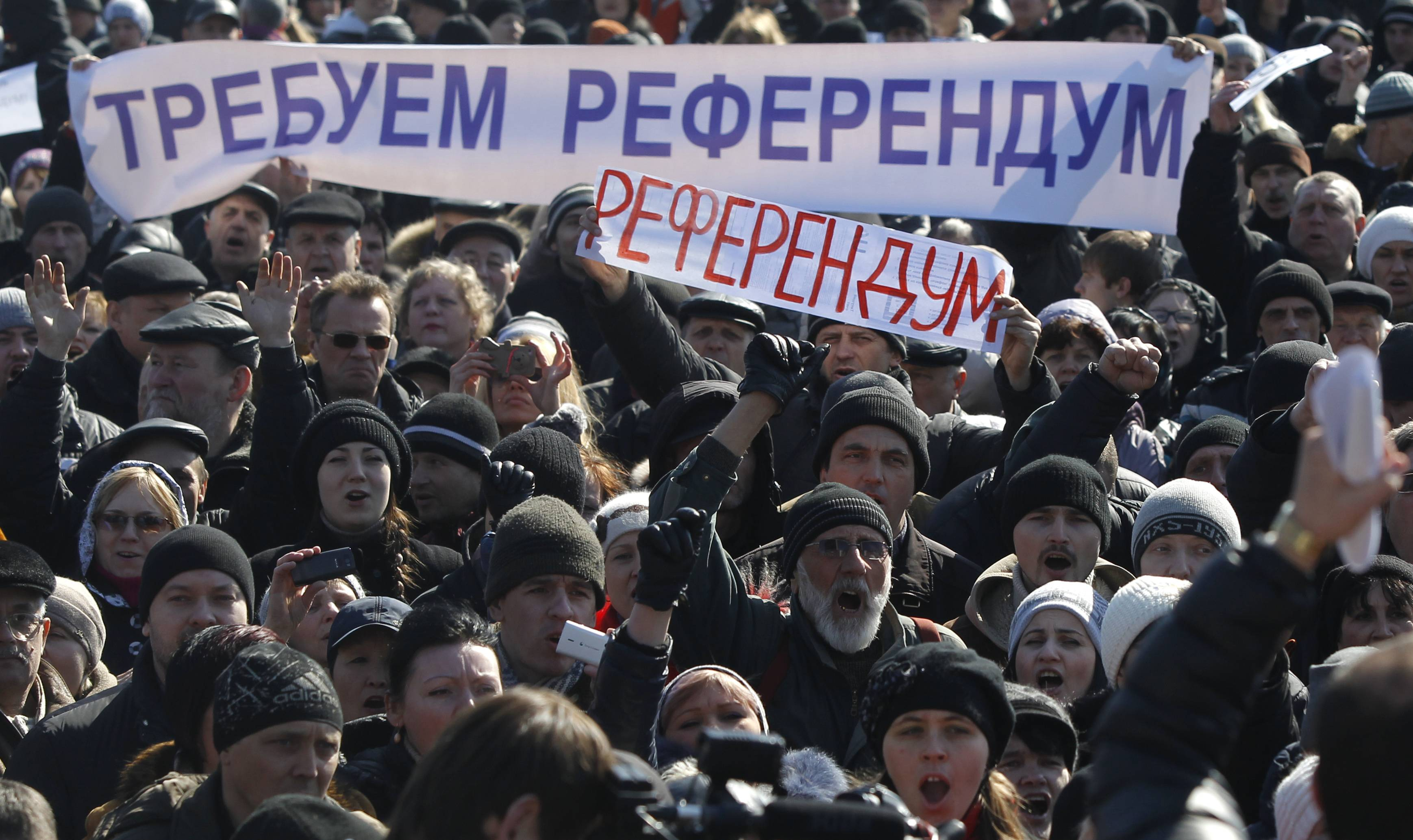"People hold a banner reading, ""We demand a referendum"" as they shout slogans during a pro Russian rally Saturday in Donetsk, Ukraine."