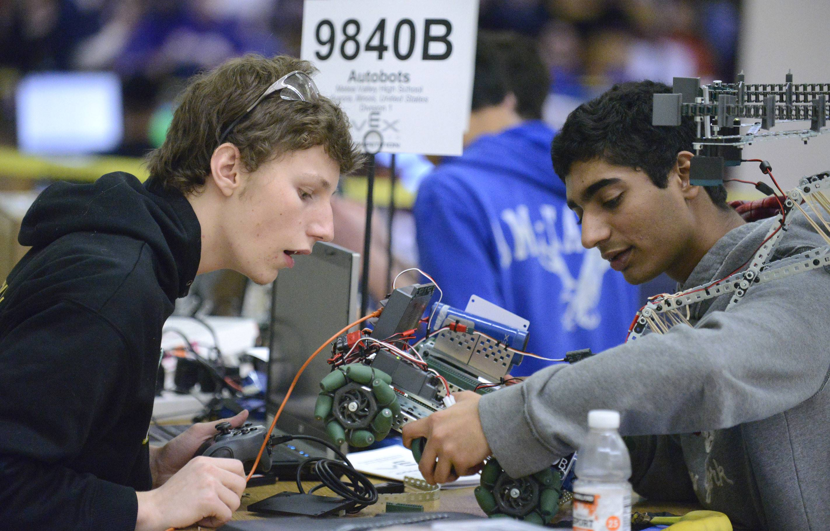 Ryan Luckinbill, 17, left, and Vignesh Sarathy, 18, of Metea Valley High School's Autobots robotics team work on their robot before the start of the Illinois VEX Robotics state championships Saturday at Batavia Middle School.