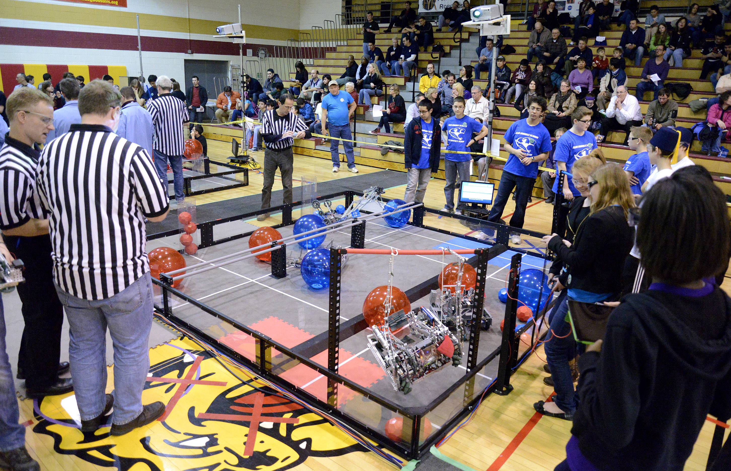 Gabby Garbaccio and Katie Miller, both 14 and from Batavia, wait while judges tally scores after their robot from team Cobalt competed in a first-round match in the Illinois VEX Robotics state championships Saturday at Batavia Middle School. They are on the right, wearing safety glasses.