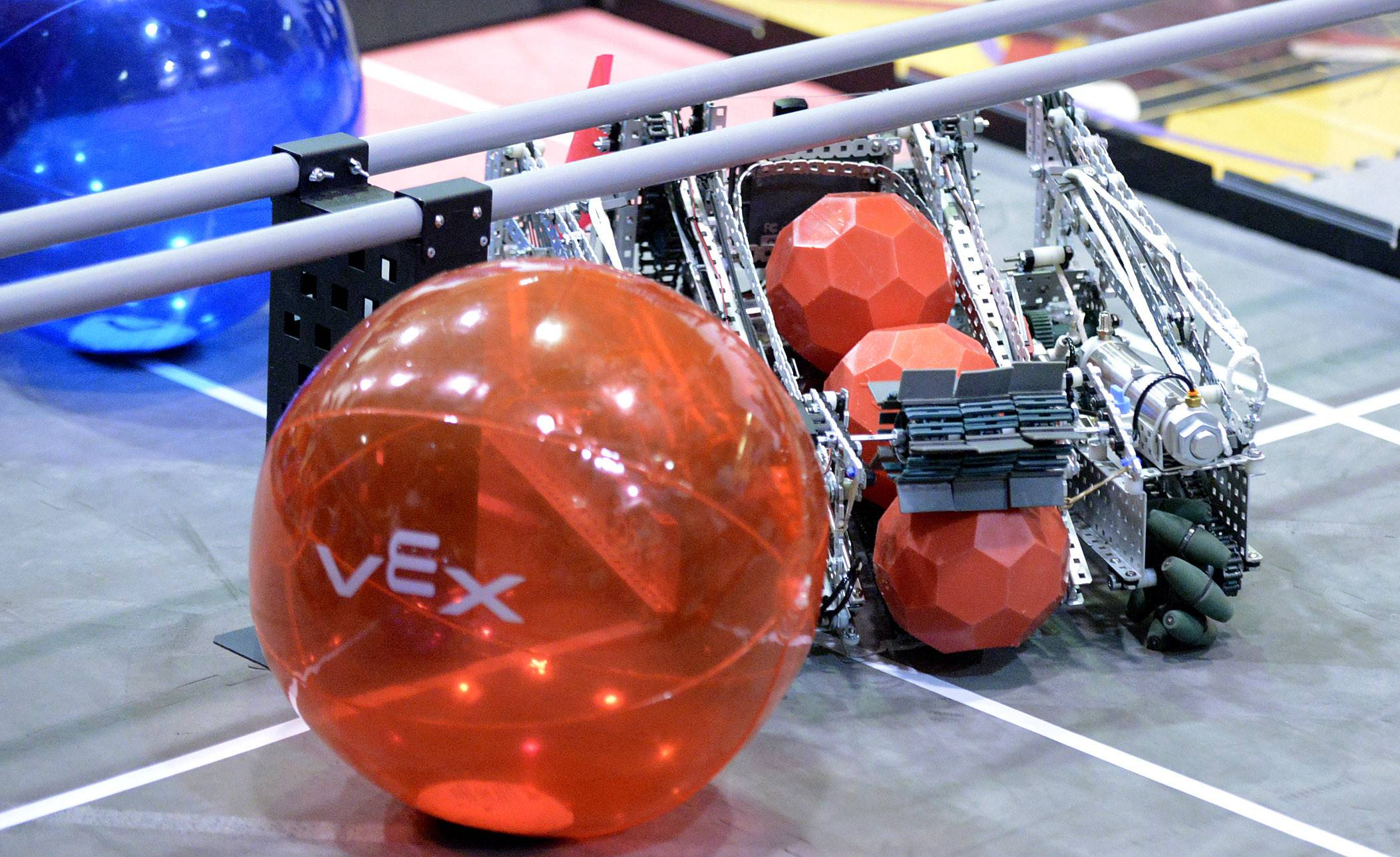 The robot from team Cobalt of the Fox Valley Robotics group out of Batavia gathers small plastic balls using a paddle, which then were carried across the mat to be deposited in a tall container during a first-round match in the Illinois VEX Robotics state championship at Batavia Middle School on Saturday, March 7.