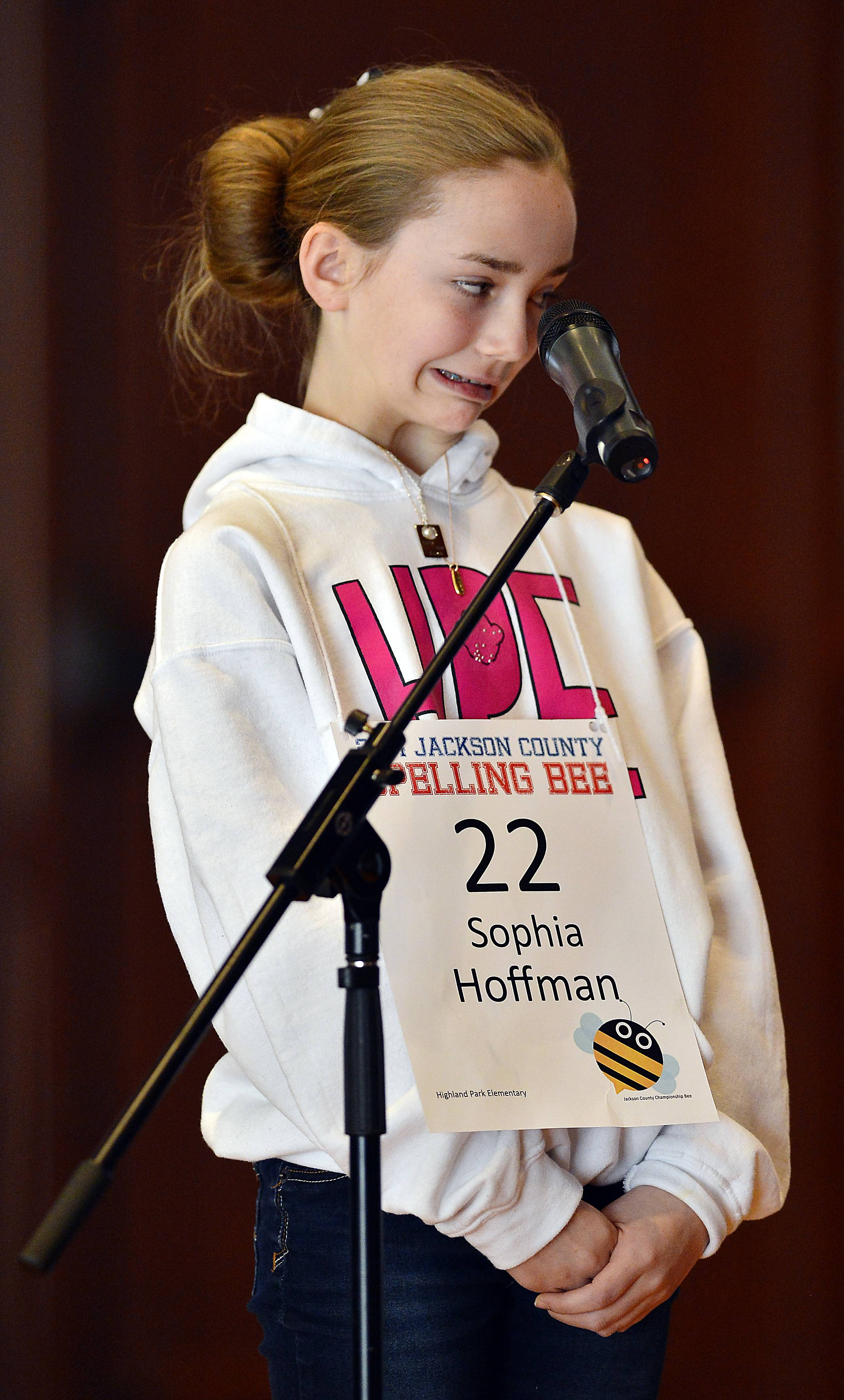 Sophia Hoffman reacts Saturday as she spells a word, which she got correct, during the continuation of the Jackson County Spelling Bee against Kush Sharma, right, at the Central Library in Kansas City, Mo.
