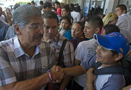 San Salvador Mayor Norman Quijano, the candidate of the Nationalist Republican Alliance, known as ARENA, shakes hands with a supporter who is waiting in line to acquire his national identification card that will allow him to vote, in San Salvador, El Salvador, Friday, March 7, 2014.