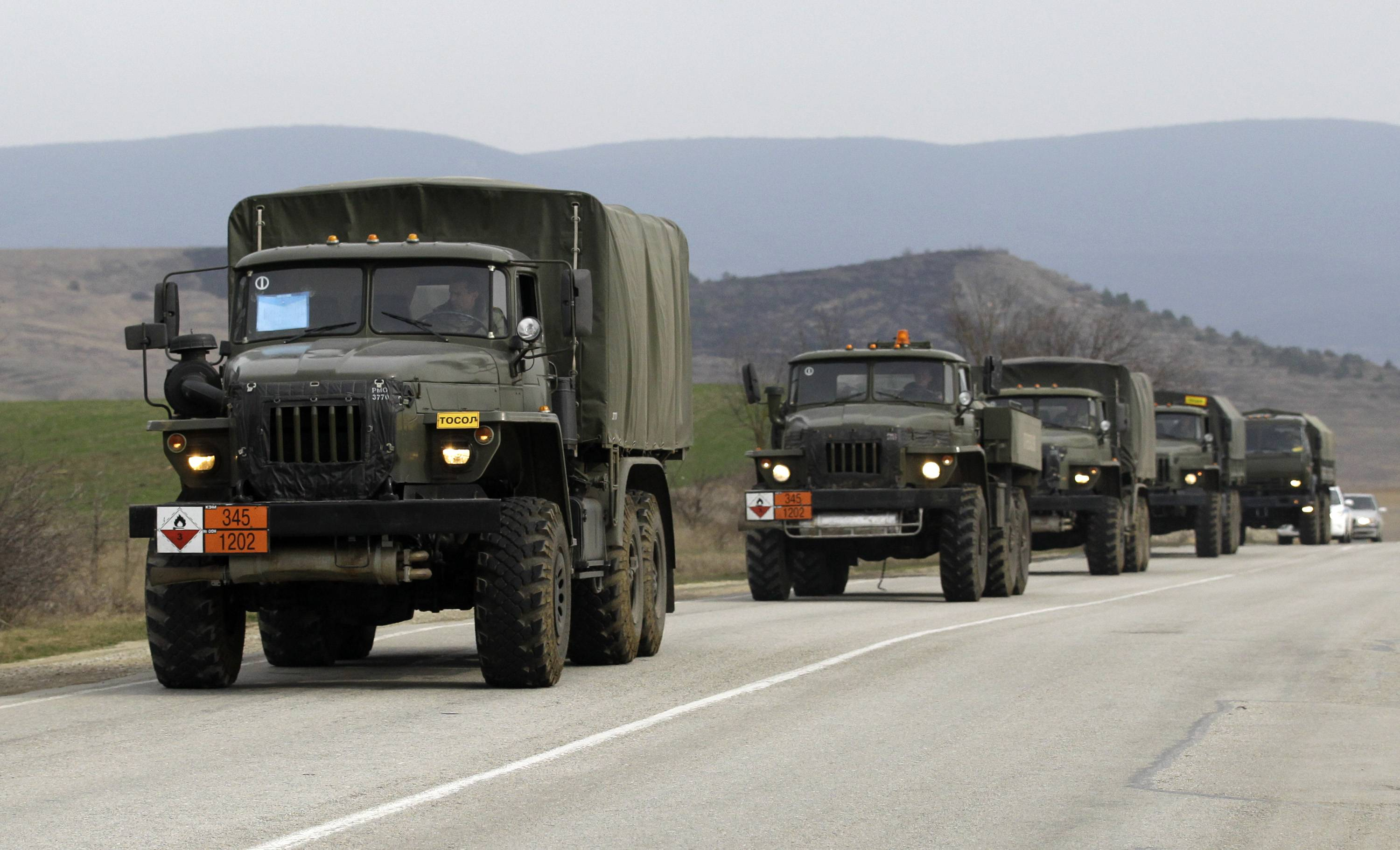 A convoy of military vehicles bearing no license plates travels on the road from Feodosia to Simferopol in the Crimea, Ukraine, Saturday, March 8, 2014. More than 60 military trucks bearing no license plate numbers was headed from the eastern city of Feodosia toward the city of Simferopol, the regional capital.