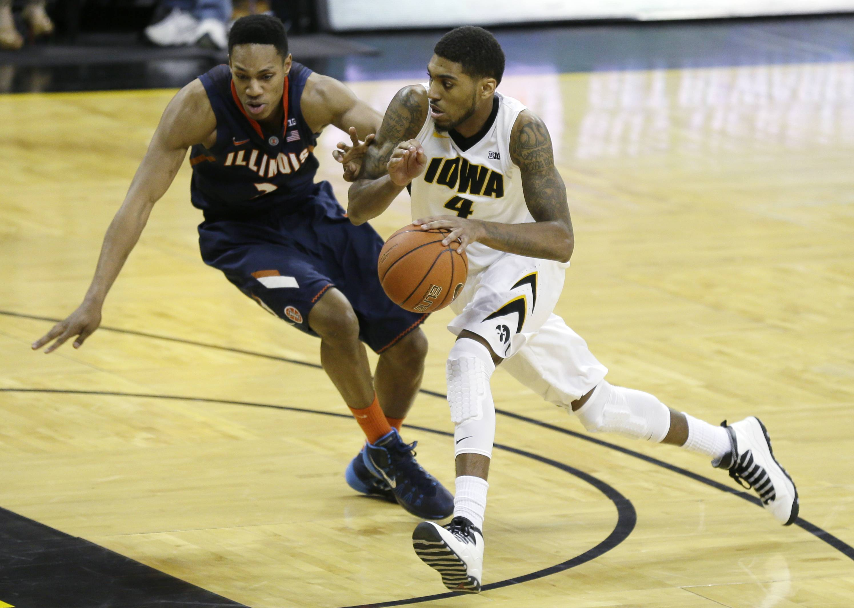 Iowa guard Devyn Marble, right, drives past Illinois guard Joseph Bertrand during the second half of an NCAA college basketball game on Saturday, March 8, 2014, in Iowa City, Iowa.