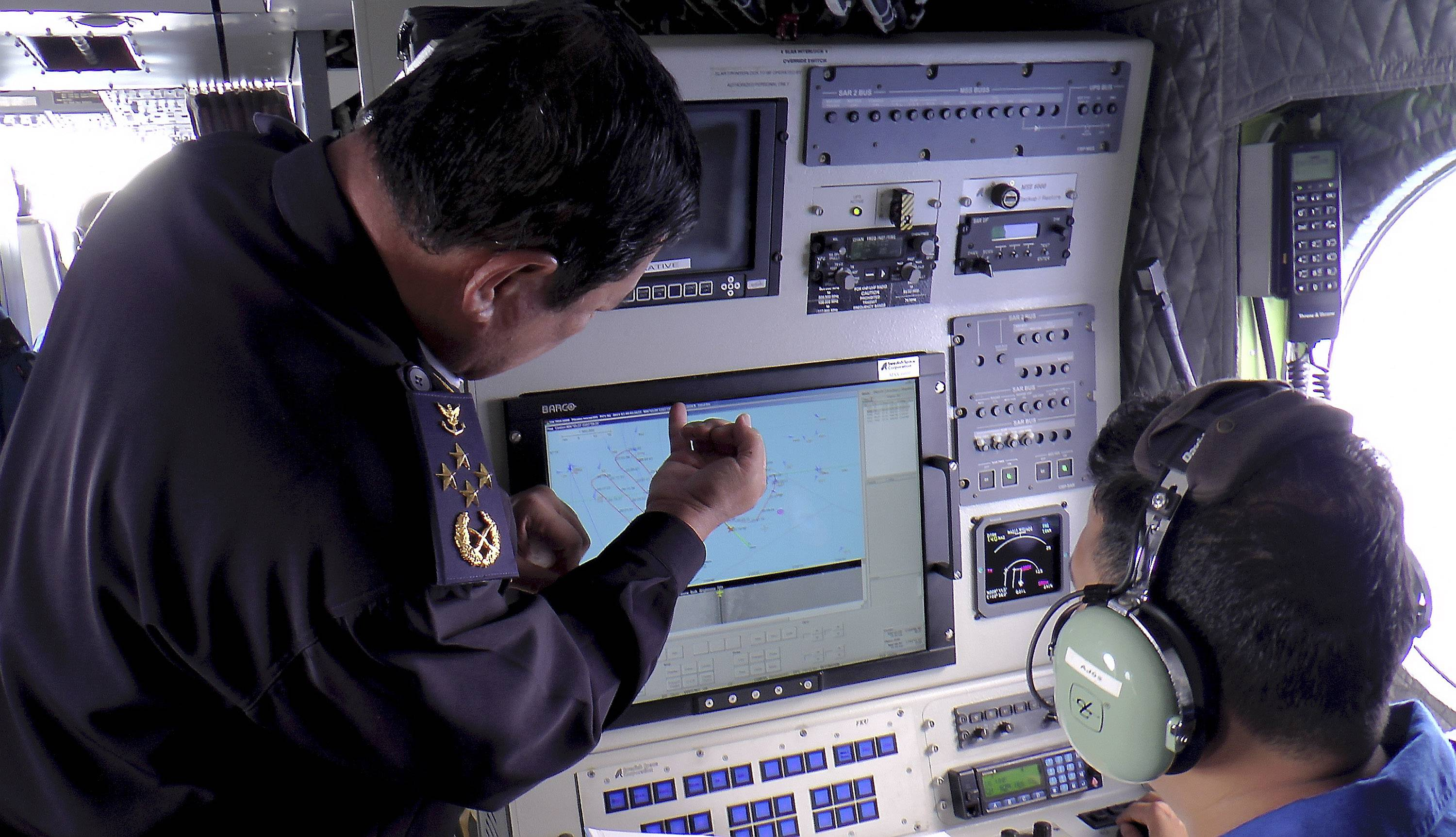 Director General of the Malaysian Maritime Enforcement Agency Admiral Mohd Amdan Kurish, left, checks radar Sunday during a search for the missing Malaysia Airlines plane off Tok Bali Beach in Kelantan, Malaysia. Military radar indicates the missing Boeing 777 jet may have turned back, Malaysia's air force chief said Sunday as scores of ships and aircraft from across Asia resumed a hunt for the plane and its 239 passengers.