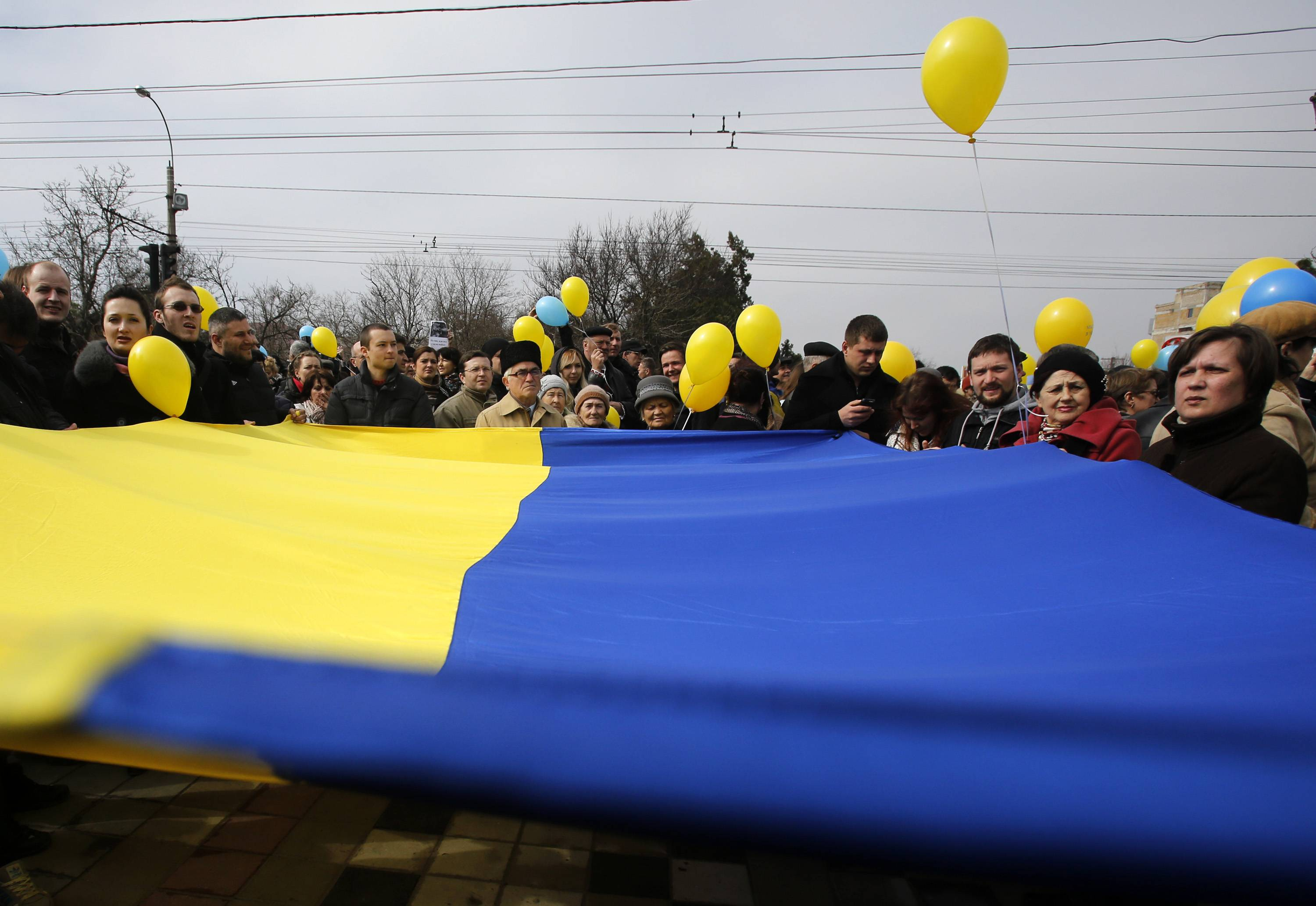 "People hold a Ukrainian flag Thursday during a rally against the breakup of the country in Simferopol, Crimea. As separatists in Crimea kept up pressure for unification with Moscow, Ukraine on Sunday solemnly commemorated the 200th anniversary of the birth of its greatest poet, with the prime minister vowing not to give up ""a single centimeter"" of Ukrainian territory."