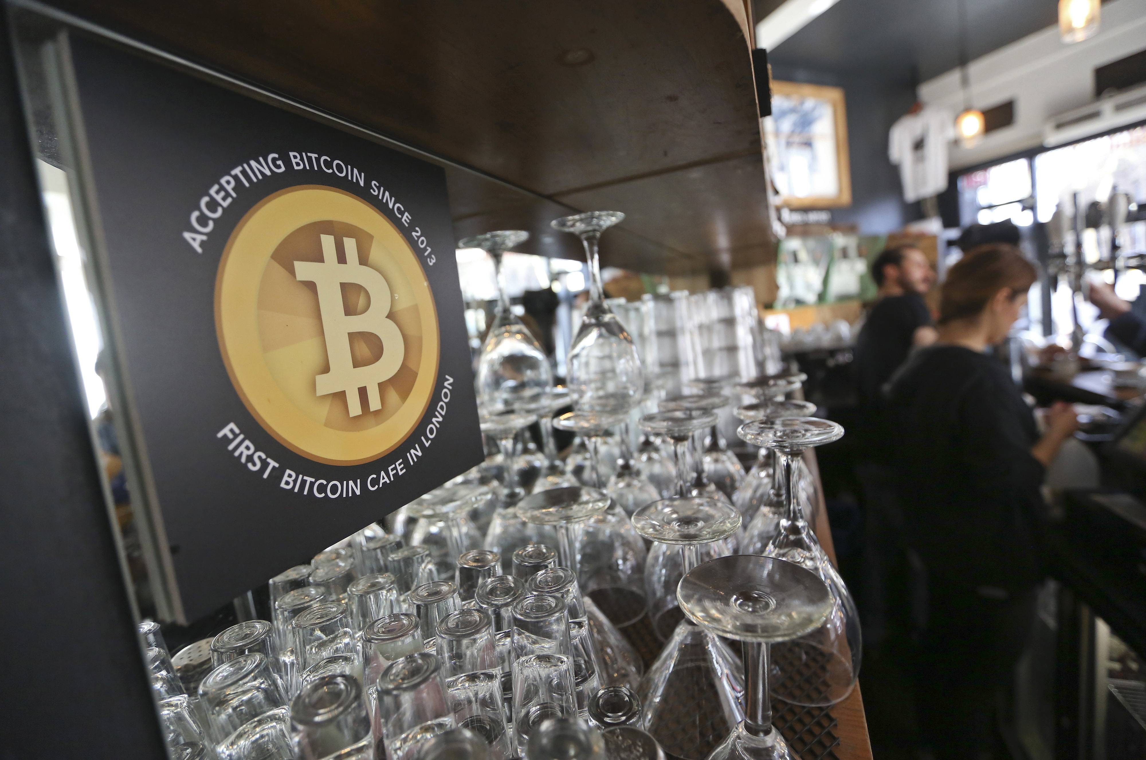 A poster alerting customers that the digital currency Bitcoin is accepted as payment sits behind the counter inside a cafe in London. Bitcoin attracted media attention last week when Tokyo-based Mt. Gox, once the biggest exchange for the digital currency, filed for bankruptcy protection after coins valued at more than $500 million went missing.