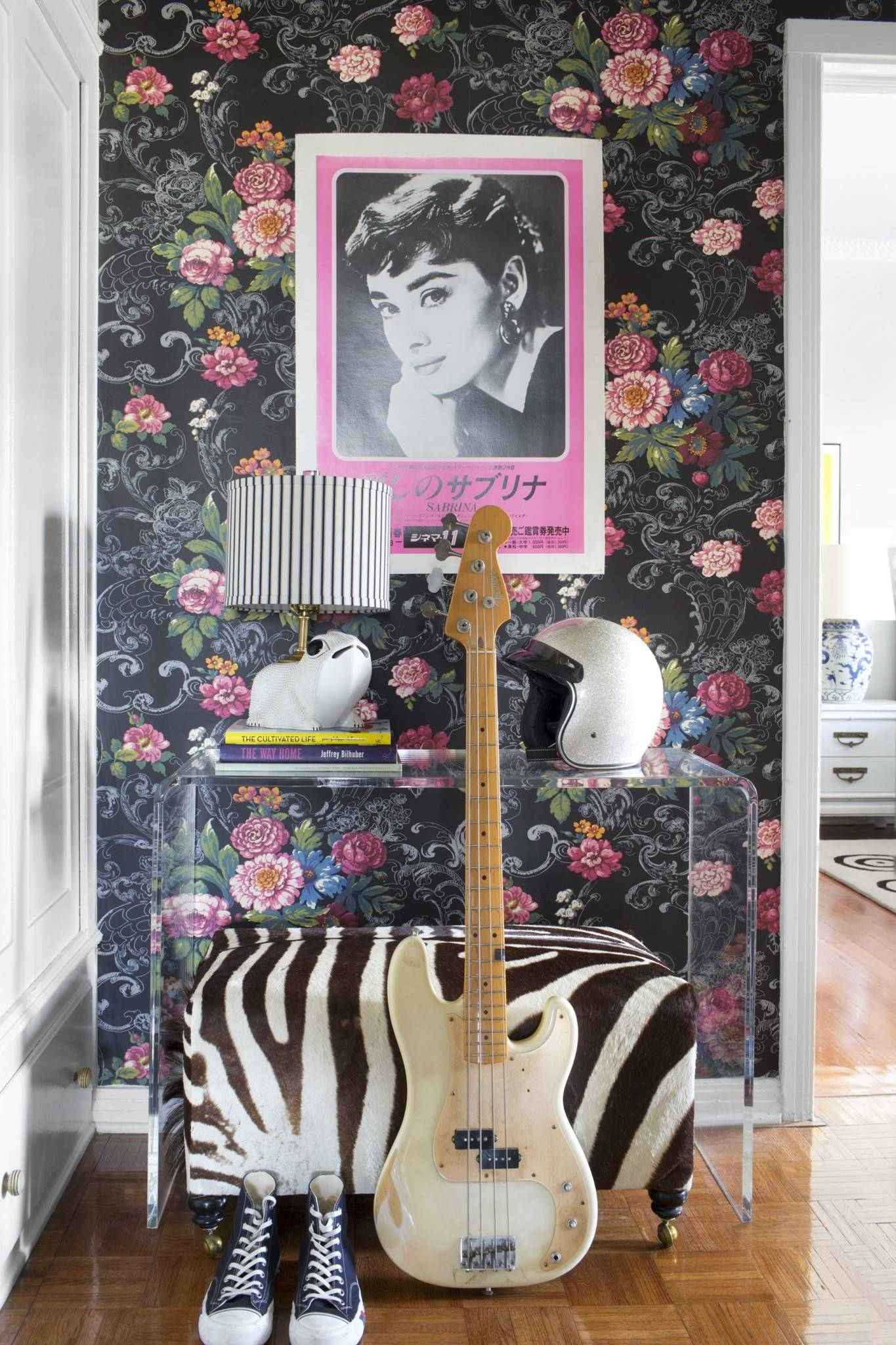 "Traditional floral wallpaper is contrasted with modern furniture and unexpected accessories like a bike helmet and a vintage Japanese poster for the movie ""Sabrina"" to create a fresh and edgy look designed by Betsy Burnham and Max Humphrey of Burnham Design, in this residence in Los Angeles."