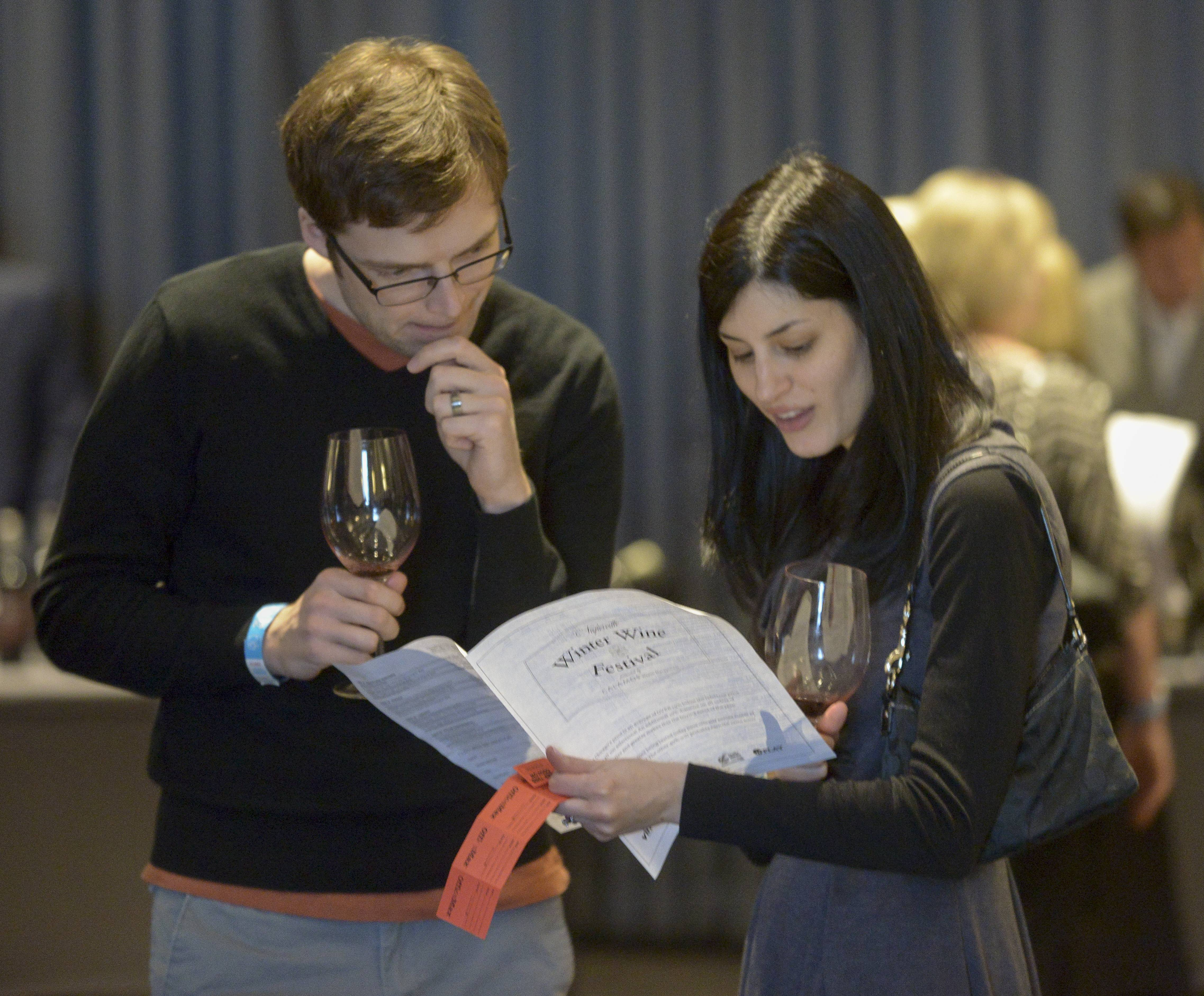 Steve Chuddy and Alesha Bondari of Villa Park look over the list of wines while attending the Naperville Winter Wine Festival at the Hotel Arista in Naperville. A portion of proceeds from the event was donated to DuPage PADS.