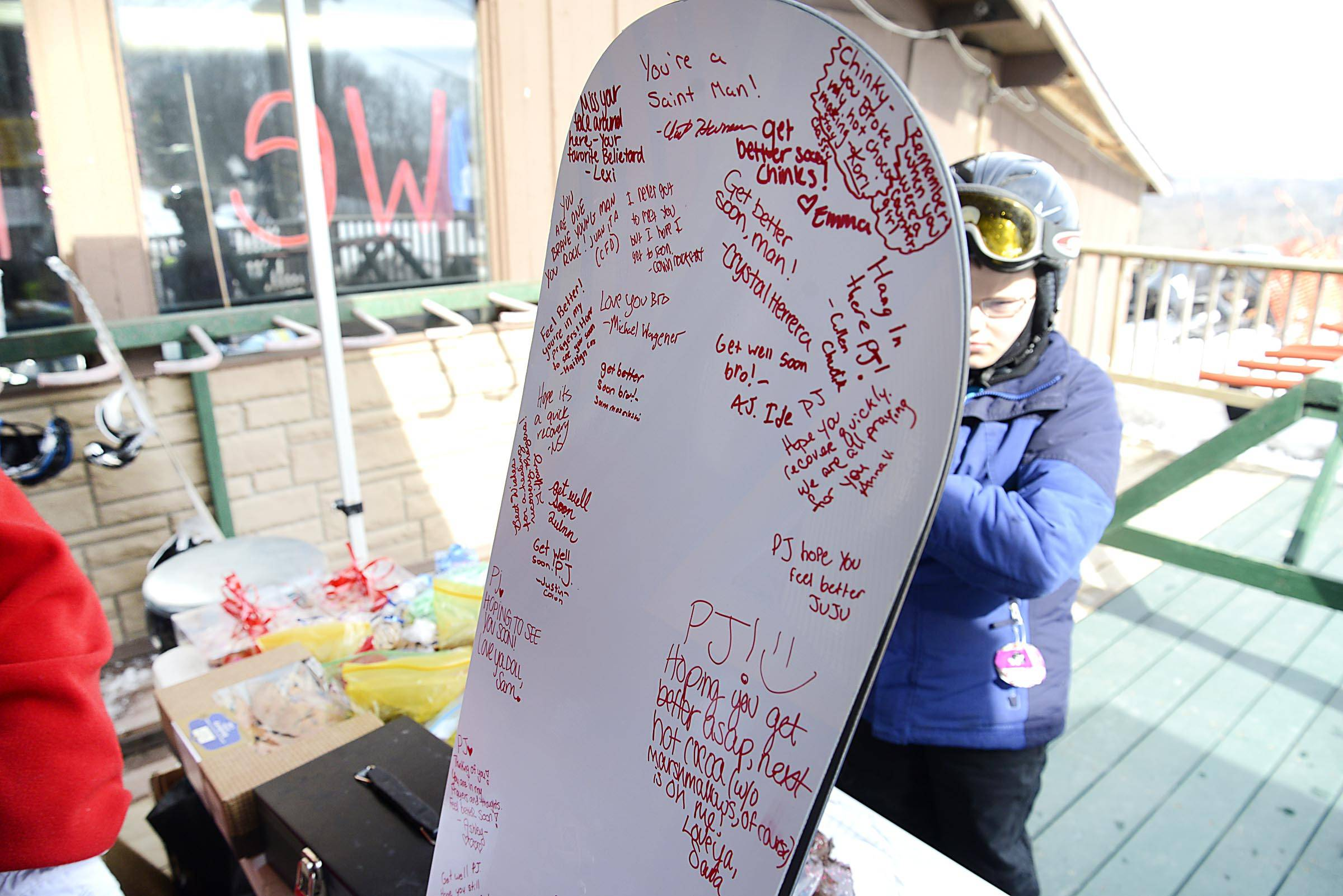 A new snowboard, autographed with well wishes from dozens of supporters, sits at a table full of donated goods being sold to raise money for a 17-year-old boy injured March 2 when he was caught in a machine at the Raging Buffalo Snow Park in Algonquin. The snowboard will be given to P.J. O'Donnell after the fundraiser.