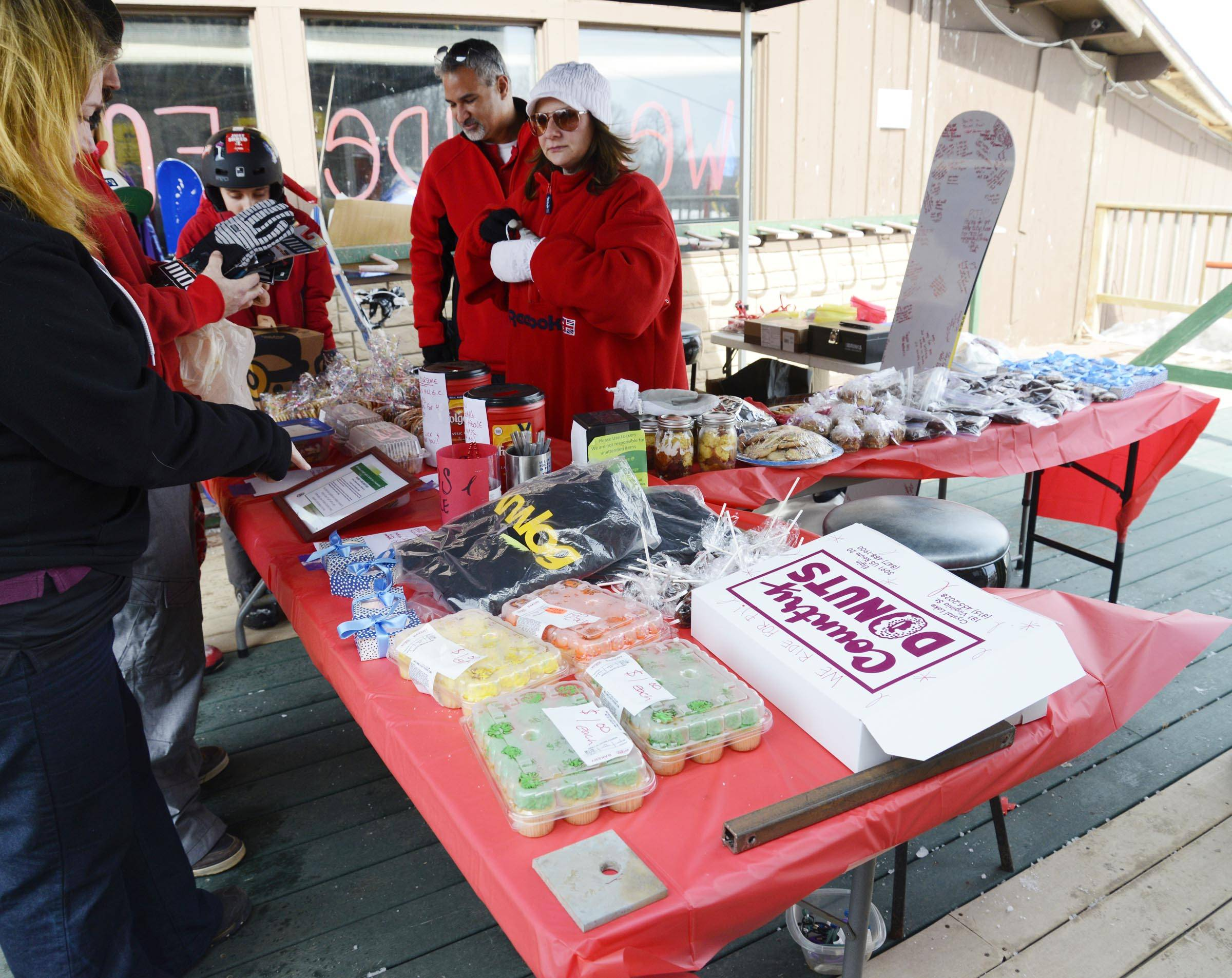 People gather Sunday at a table full of donated goods being sold to raise money for P.J. O'Donnell, the 17-year-old injured March 2 when he was caught in a machine at the Raging Buffalo Snow Park in Algonquin.