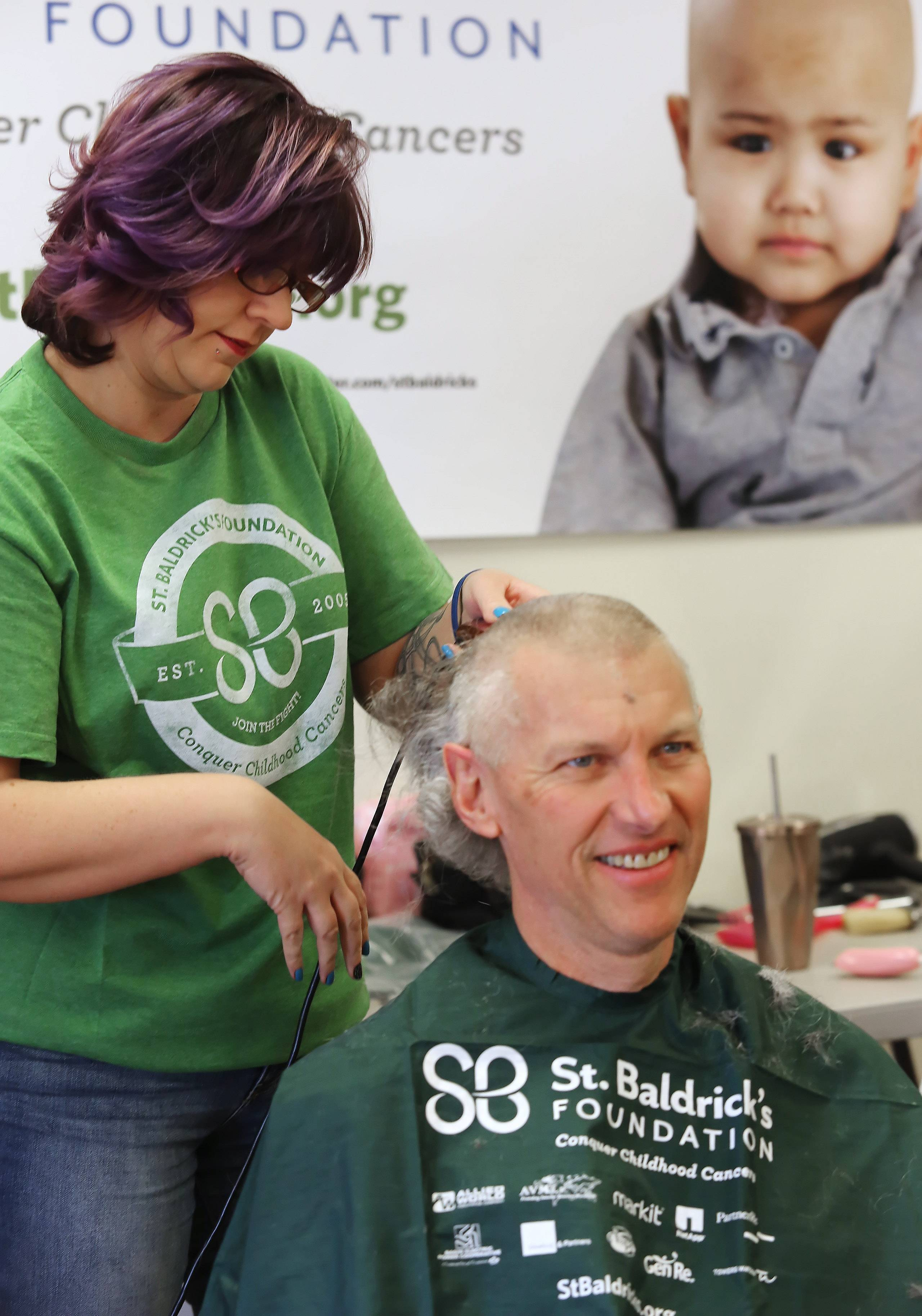 "Hair stylist Amy Lang cuts the hair of Jim McClure of Grayslake during the ""Taking It All Off for Cancer"" event Sunday at the Fox Lake Fire Department Bingo Hall. This is the seventh time McClure has undergone a shave for cancer research. He hopes to raise more than $7,000."