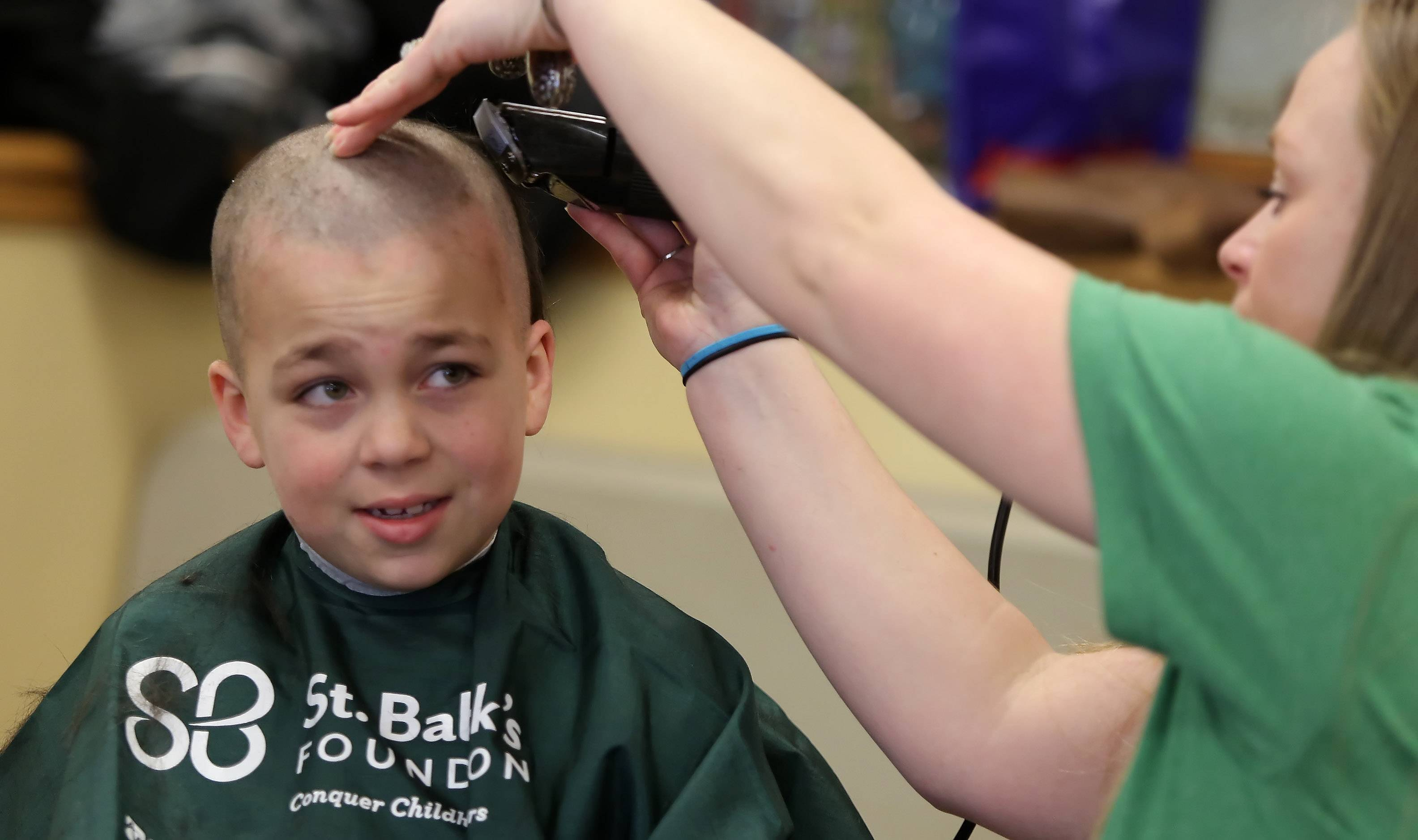 "Tyler Weidman, 8, of Grayslake sits nervously as his hair is cut by Kate LaCasse of Algonquin during the ""Taking It All Off for Cancer"" event Sunday at the Fox Lake Fire Department Bingo Hall. Firefighters, police, and the general public had their heads shaved to raise money for cancer research through the St. Baldrick's Foundation."