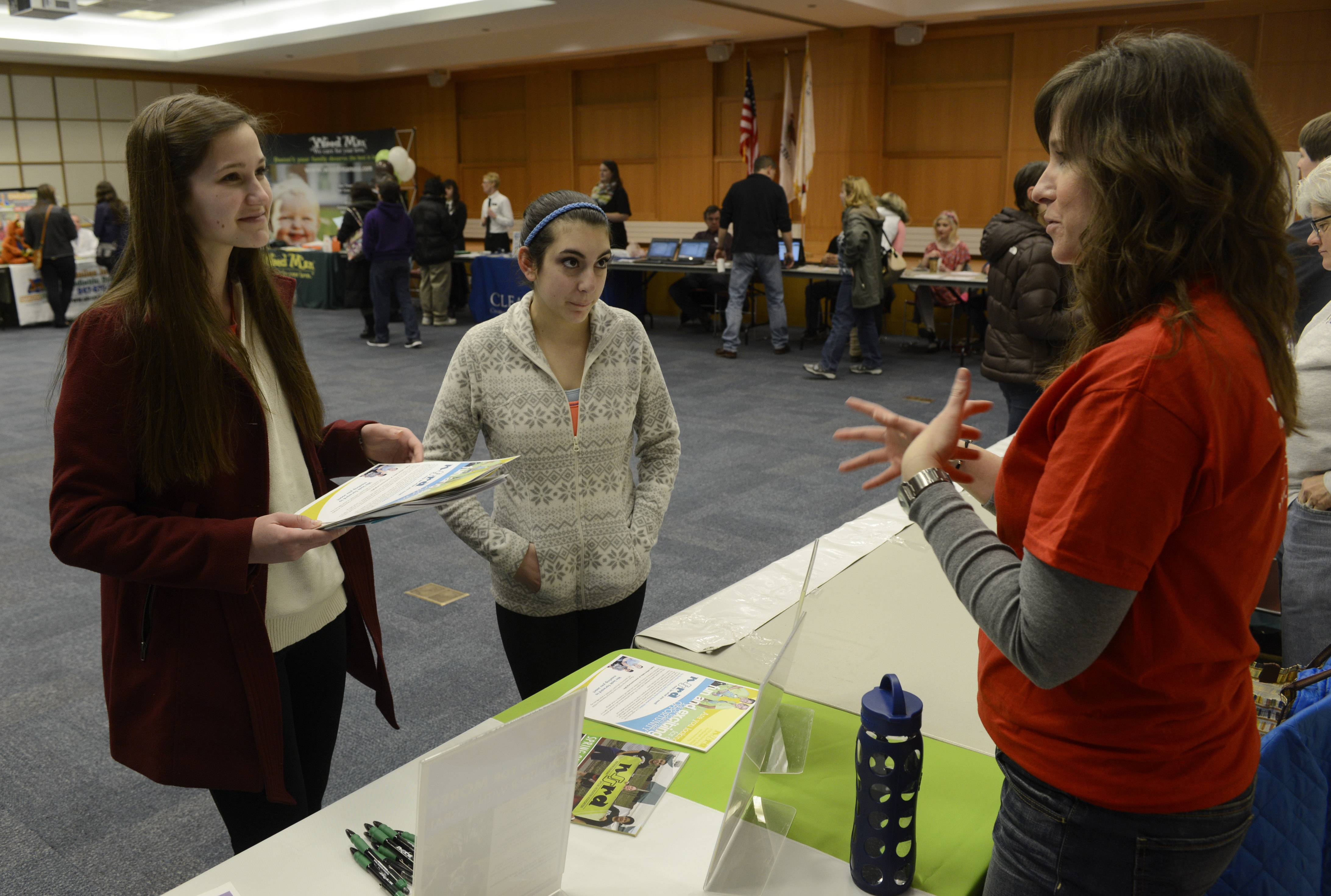 Morgan Buckley, left, and Camille Carso, both 16-year-old Hersey High School students who live in Arlington Heights, speak with Candice Cunningham, superintendent of operations for the North Suburban Special Recreation Association, during the Teen Job Fair Saturday at the Arlington Heights Memorial Library.