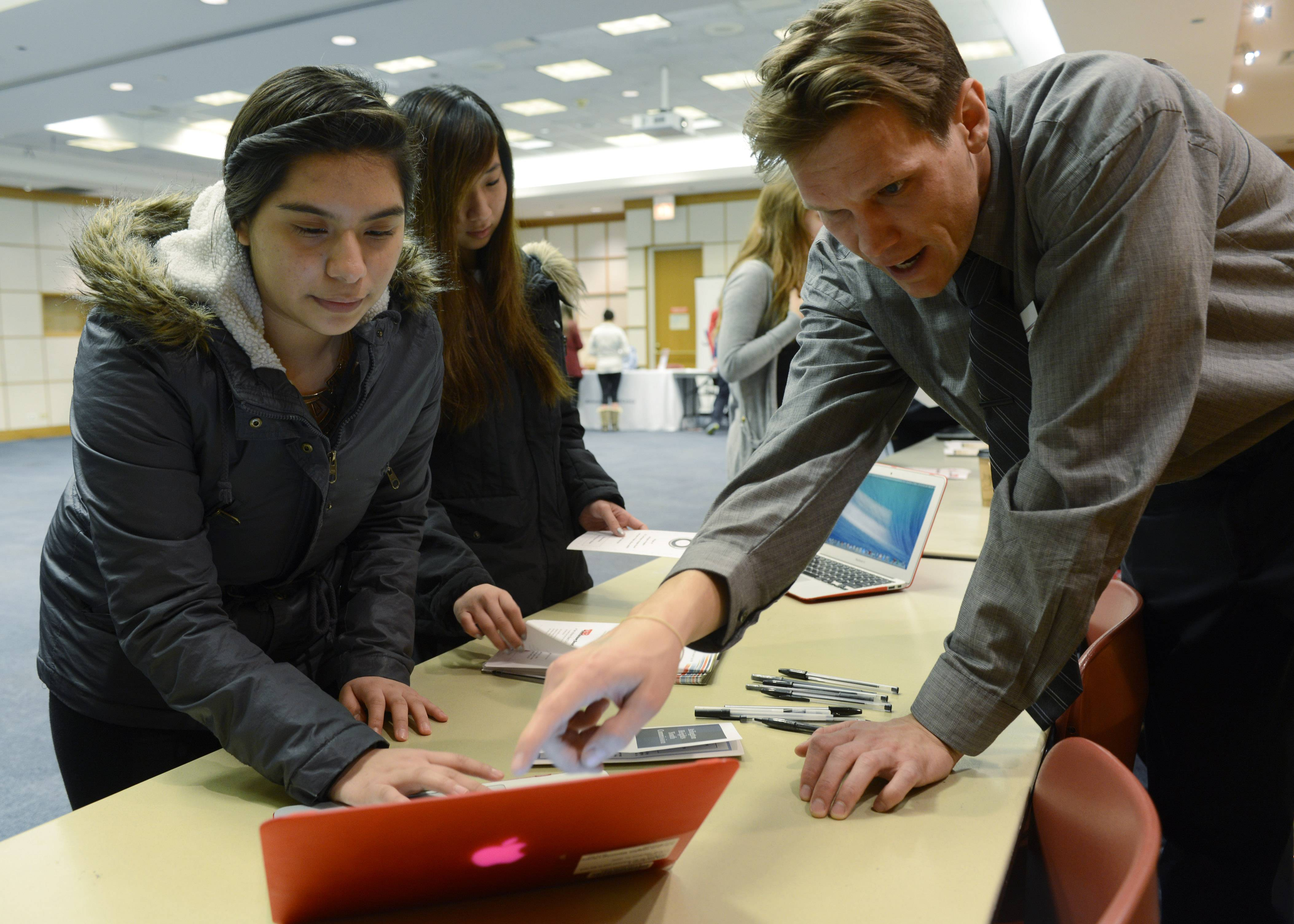 Lizbeth Melgoza, 15, left, and Vivian Tran, 16, both Hersey High School students from Mount Prospect, visit with Tom Spicer, teen services supervisor for the Arlington Heights Memorial Library, during the Teen Job Fair on Saturday at the library.