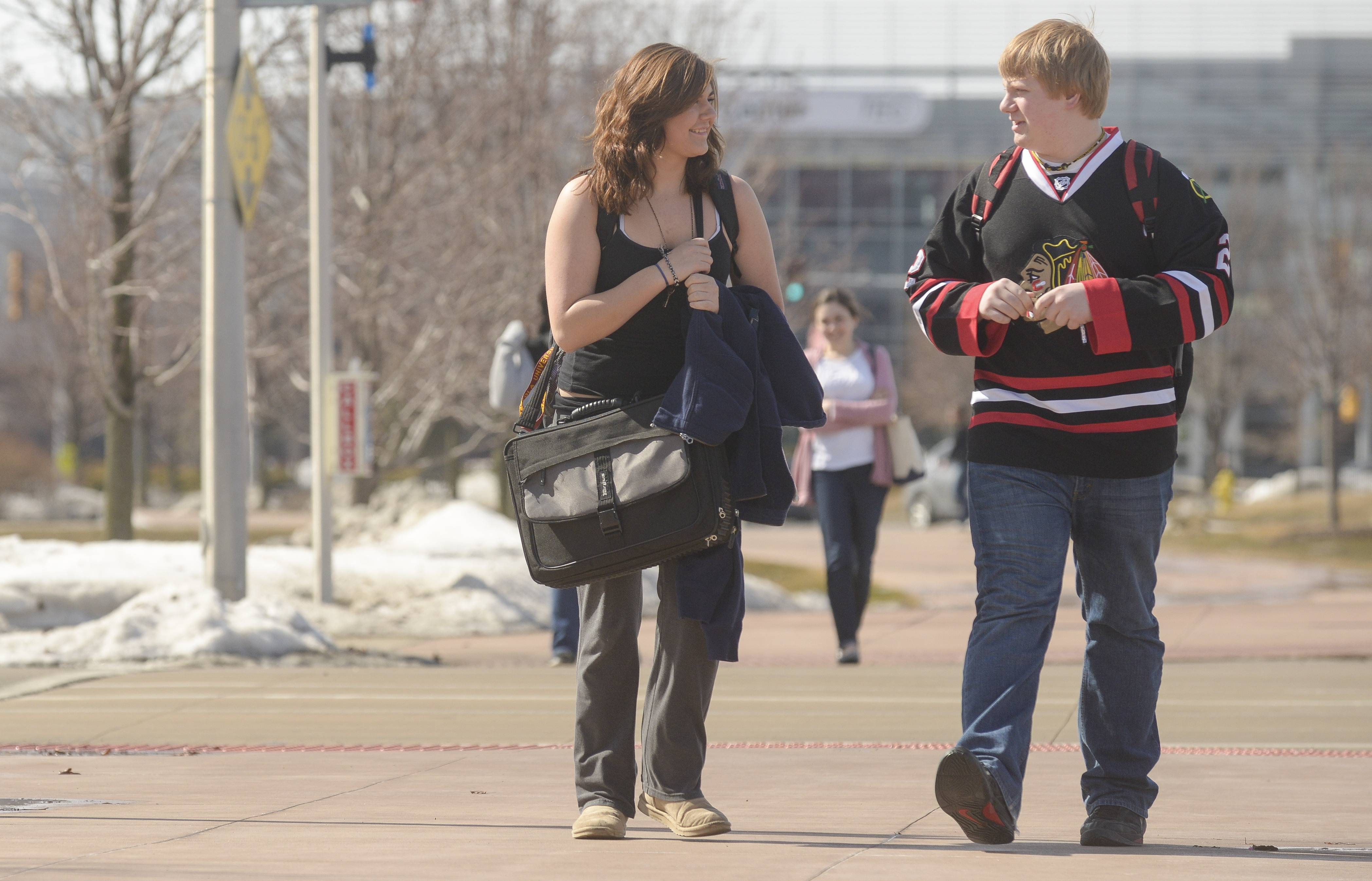 College of DuPage students Ashley Stelmack of LaGrange Park and Corey Petric of Naperville forgoing wearing jackets or even long sleeves for Stelmack as the temperatures rise into the low 50s Monday.