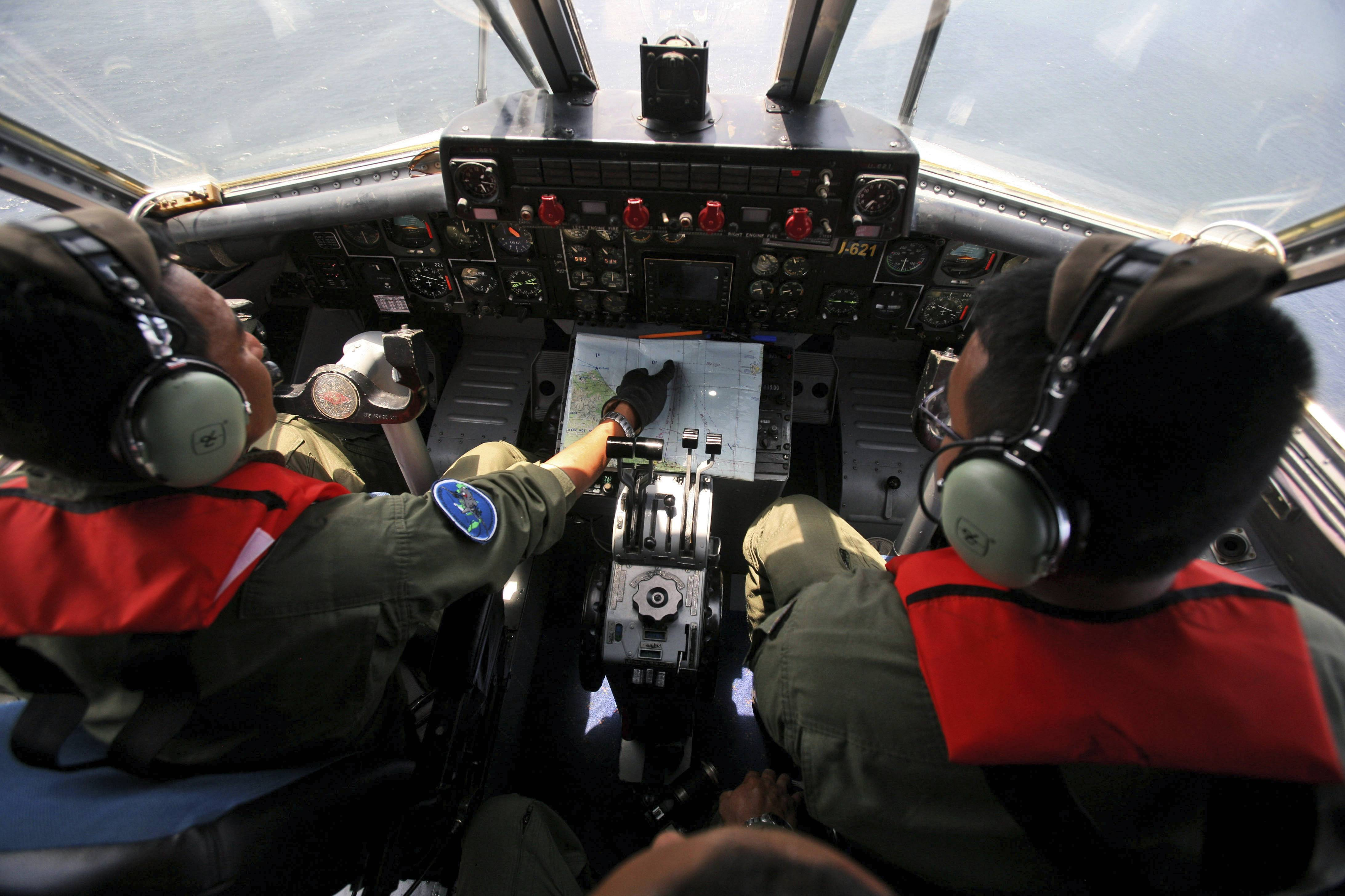 Indonesian Navy pilots Maj. Bambang Edi Saputro, left, and 2nd Lt. TriLaksono check their map during a search operation for the missing Malaysian Airlines Boeing 777 over the waters bordering Indonesia, Malaysia and Thailand near the Malacca straits Monday, March 10.