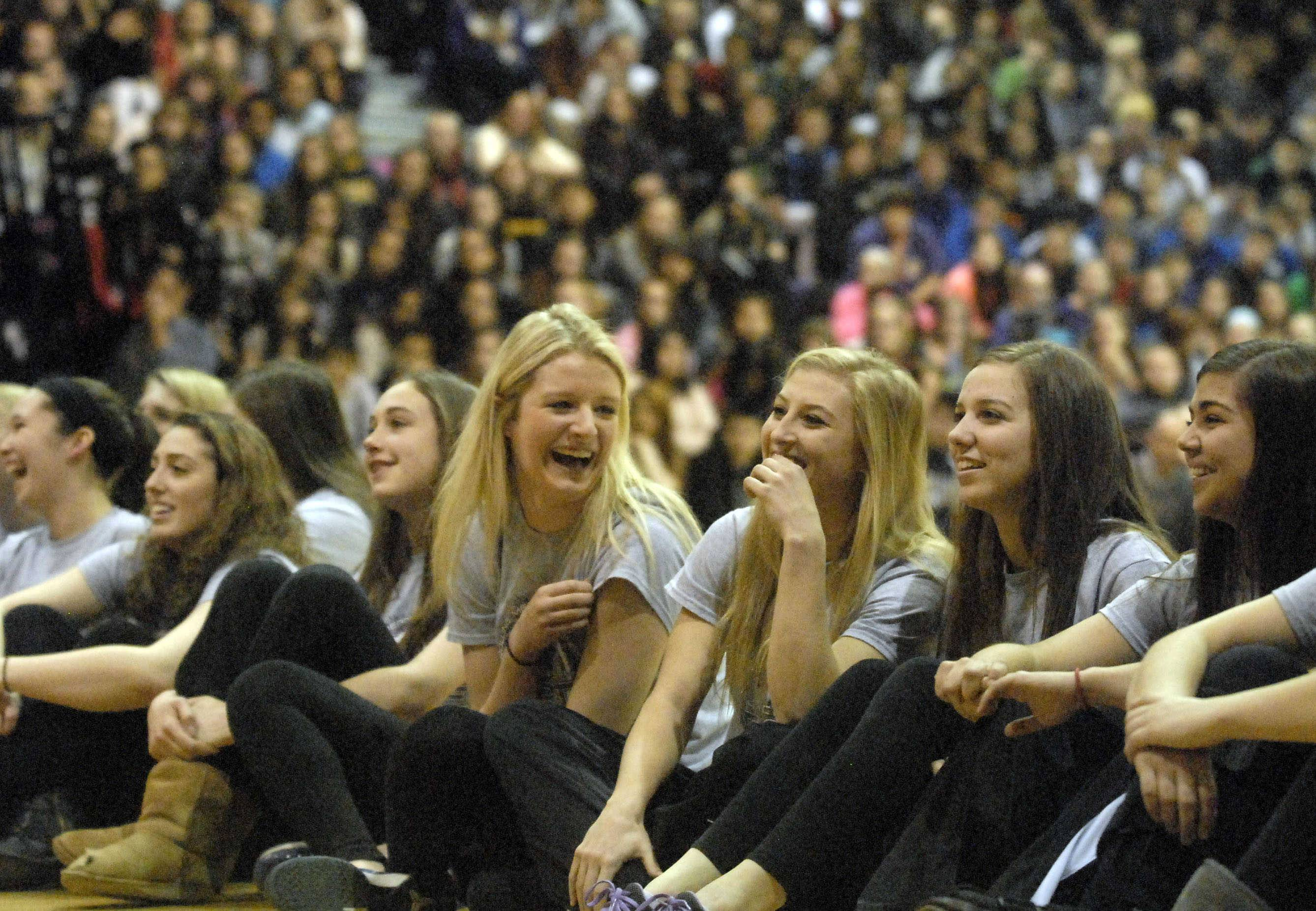 Rolling Meadows' Jenny Vliet, center, shares a laugh with teammate Jackie Kemph, center right, and others as they watch a highlight video during a pep assembly at the school on Monday.