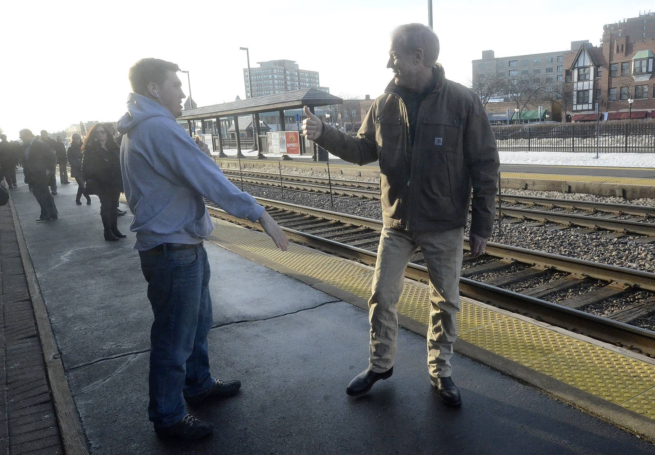 GOP gubernatorial candidate Bruce Rauner visits with voters at the Arlington Heights Metra train station Monday morning.
