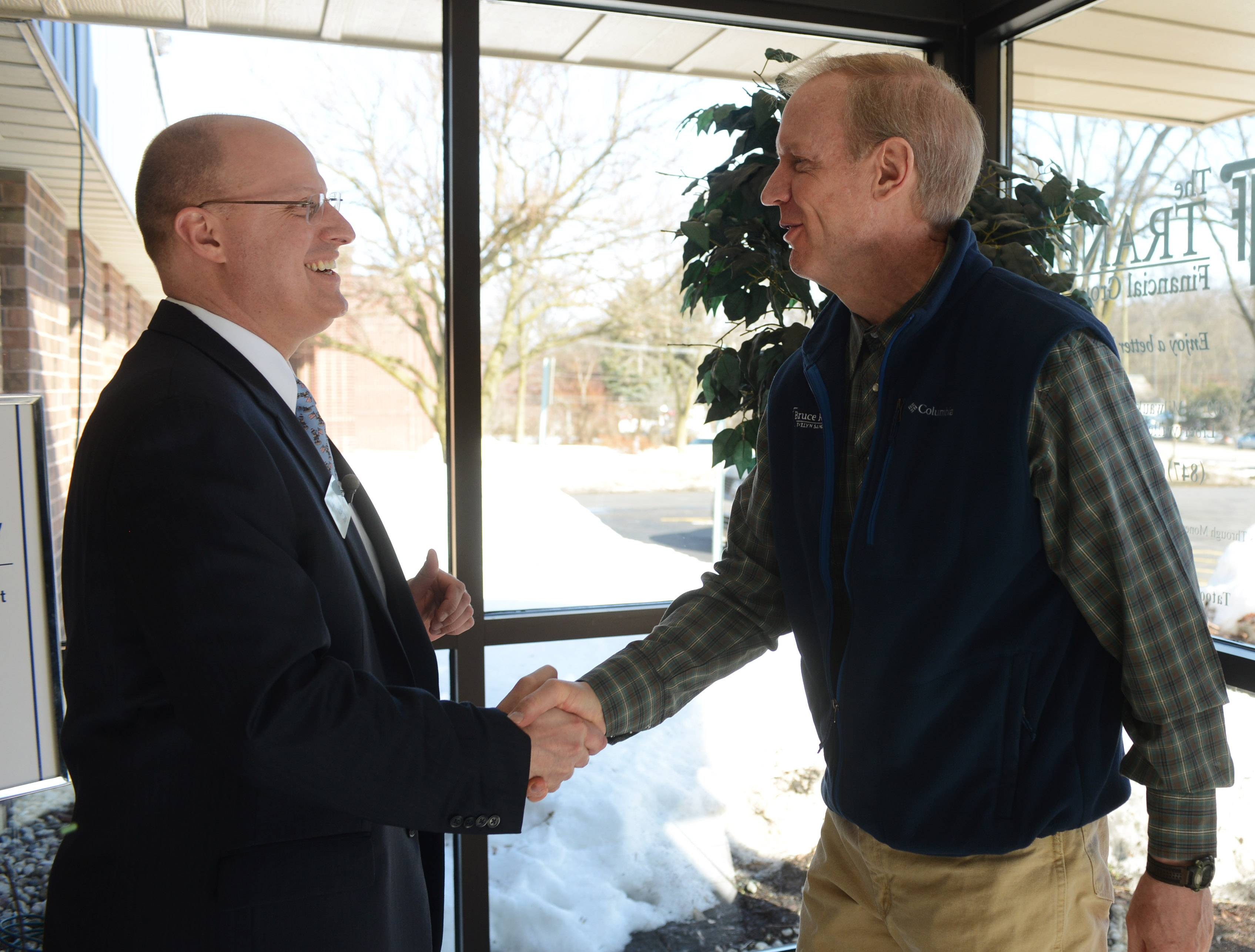 Republican gubernatorial candidate Bruce Rauner, right, meets Roch Tranel of Tranel Financial Group during a bus campaign stop in Libertyville Monday morning.