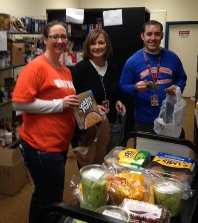 Hoffman Estates teachers Angie Rallidis, left, Debbie Miller and Jeff Davis, packing food into backpacks on Friday to send home with students.