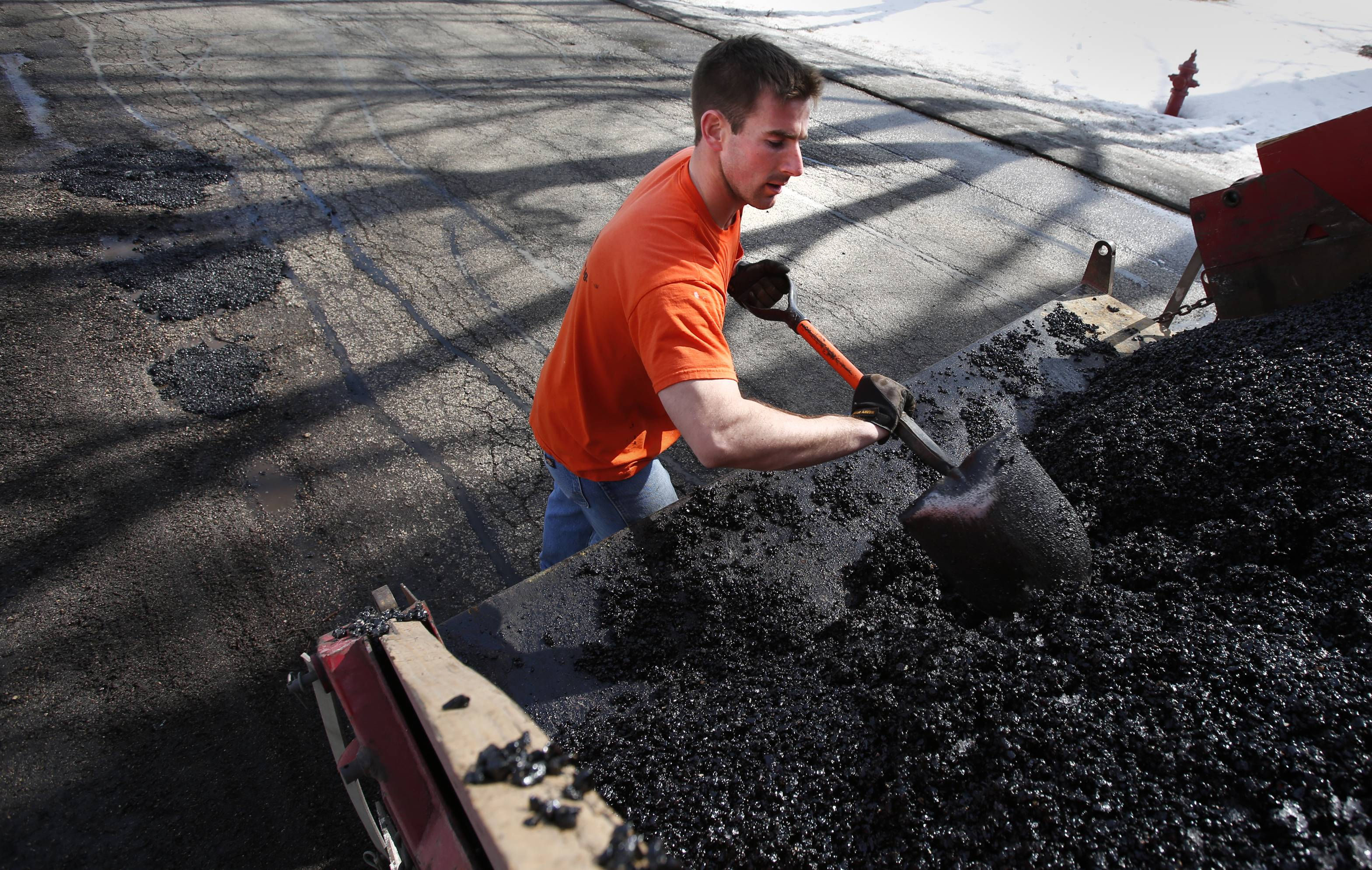Sleepy Hollow public works employee Kyle Killinger fills in potholes along Willow Drive Monday, while wearing a short-sleeved shirt. Even though pothole season continues, at least those that work outside got a huge break Monday with springlike temperatures.