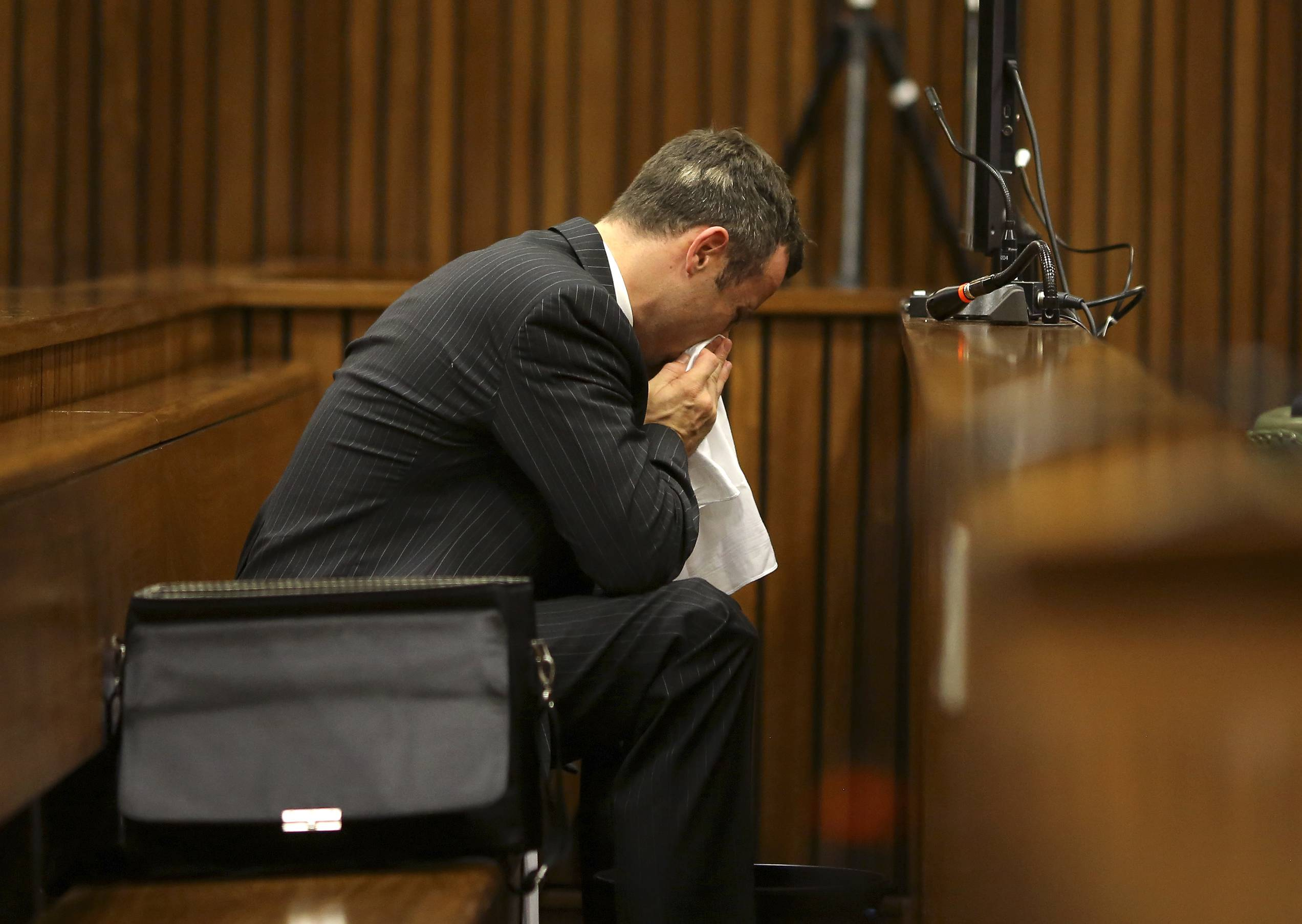 Oscar Pistorius blows his nose  after reaching for a bucket as he listened to cross questioning about the events surrounding the shooting death of his girlfriend Reeva Steenkamp, in his second week in court during his trial in Pretoria, South Africa, Monday.