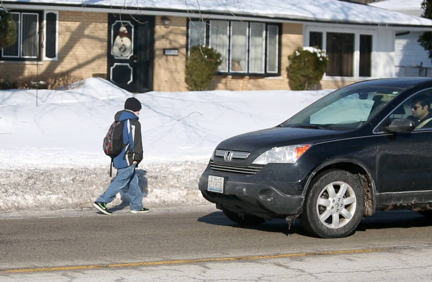 Cars whiz right by Matthew Sim, 12, as he walks to Enders-Salk Elementary School on Salem Avenue because some sidewalks are impassable in Schaumburg.